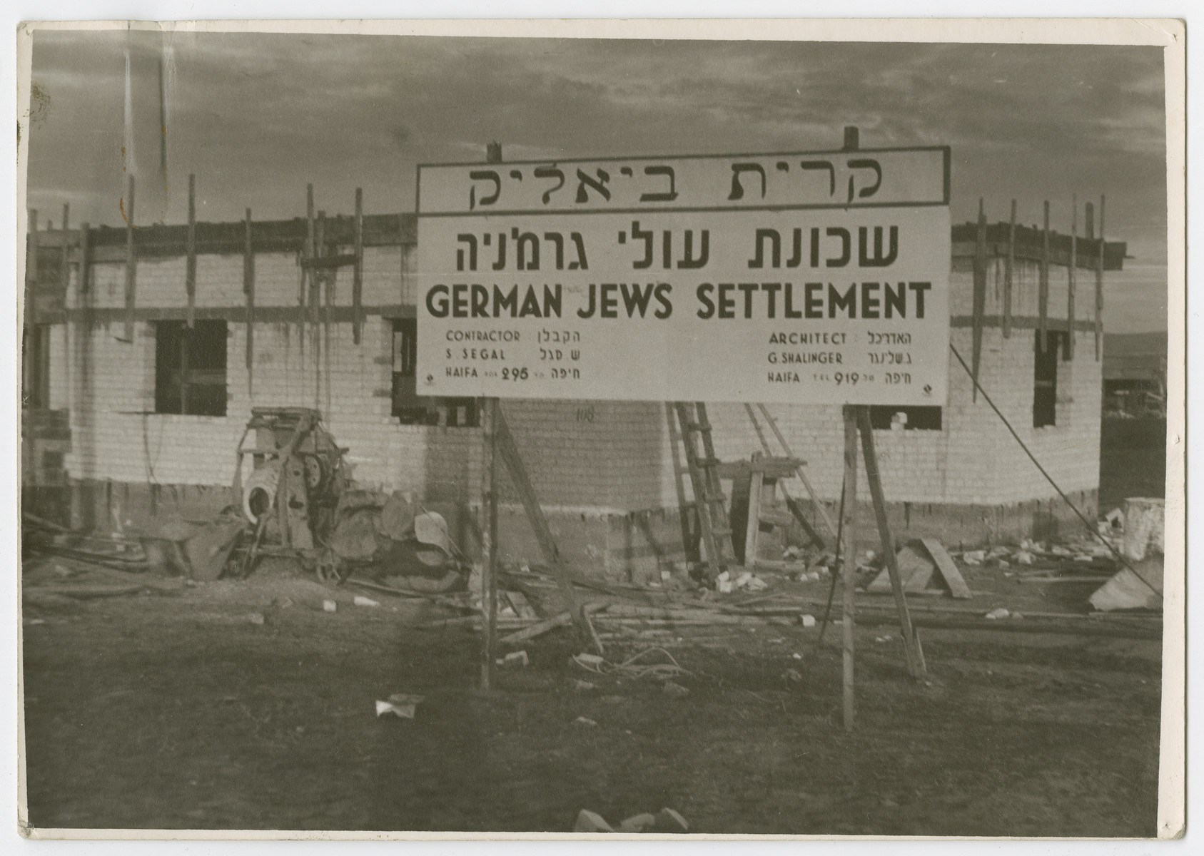 """View of the sign announcing the construction of Kiryat Bialik, a new settlement for German Jews.  Photograph is used on page 210 of Robert Gessner's """"Some of My Best Friends are Jews."""" The typed caption attached the photograph reads, """"One of the German Jewish colonies constructed in the outskirts of Haifa."""""""