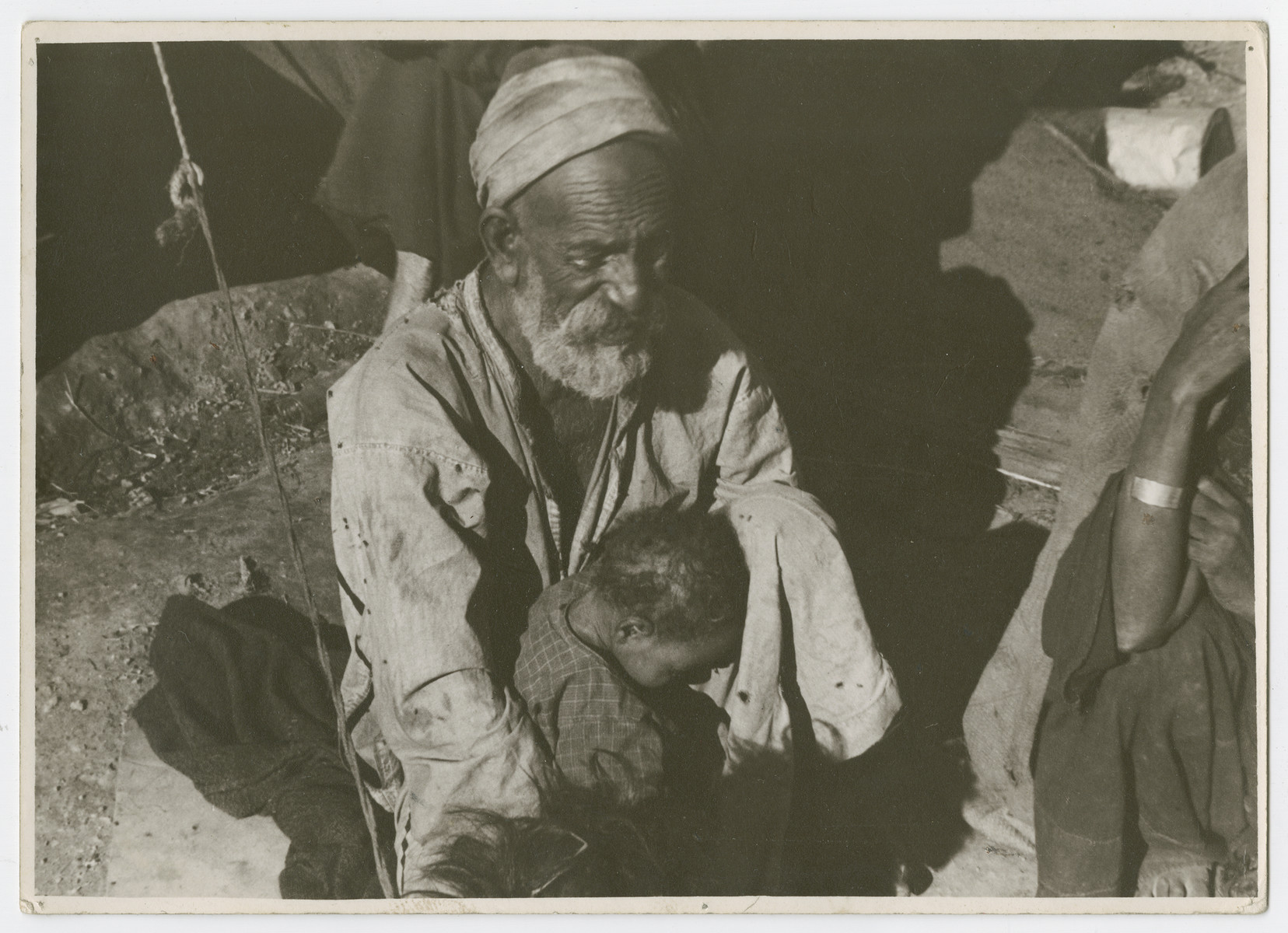 "An older man and young child [probably Sephardic] sit outsie a tent.  Photograph is used on page 253 of Robert Gessner's ""Some of My Best Friends are Jews."""