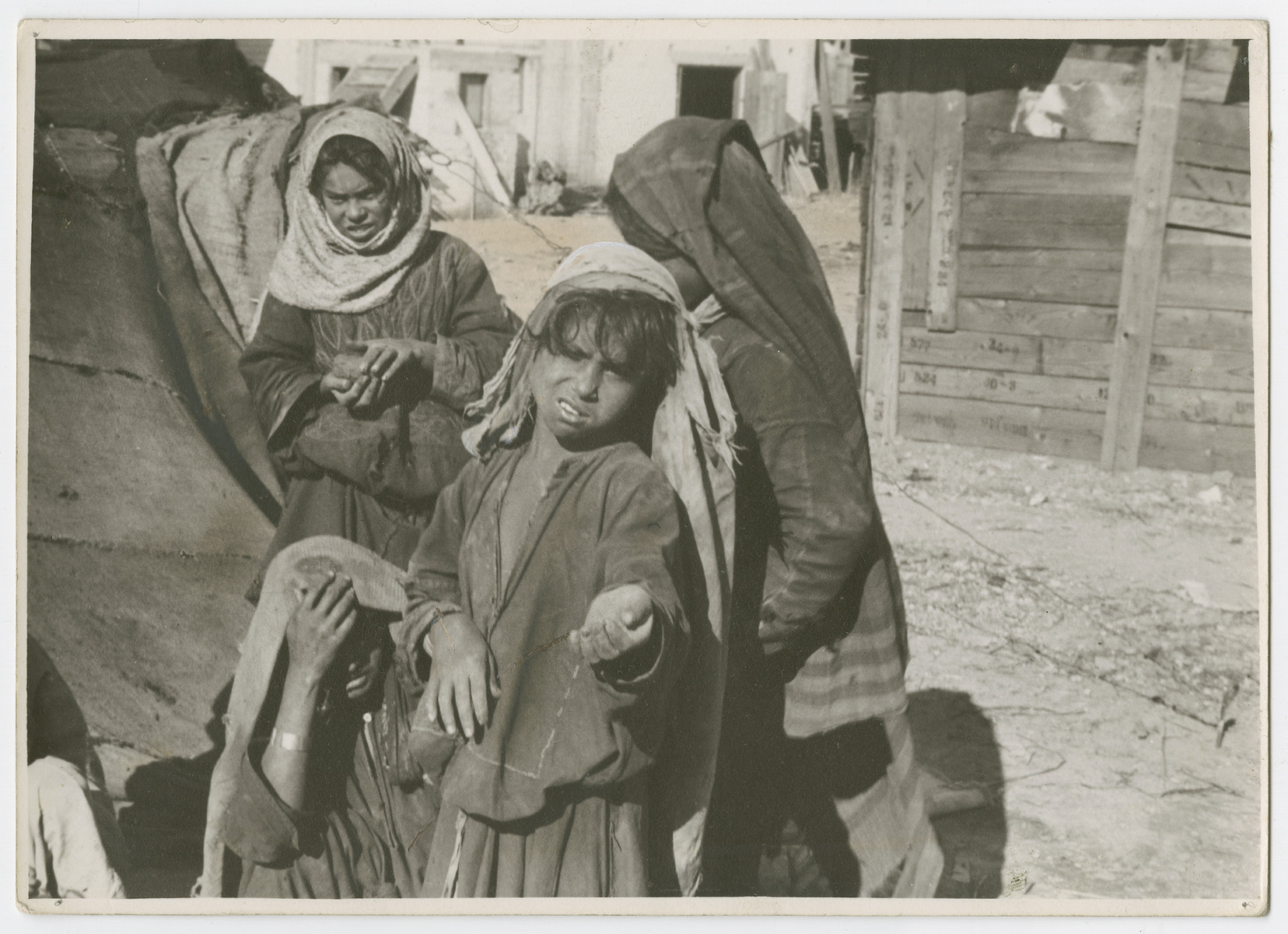 "Children [probably Arab] beg in an unidentified location in Palestiine.  Photograph is used on page 244 of Robert Gessner's ""Some of My Best Friends are Jews."""