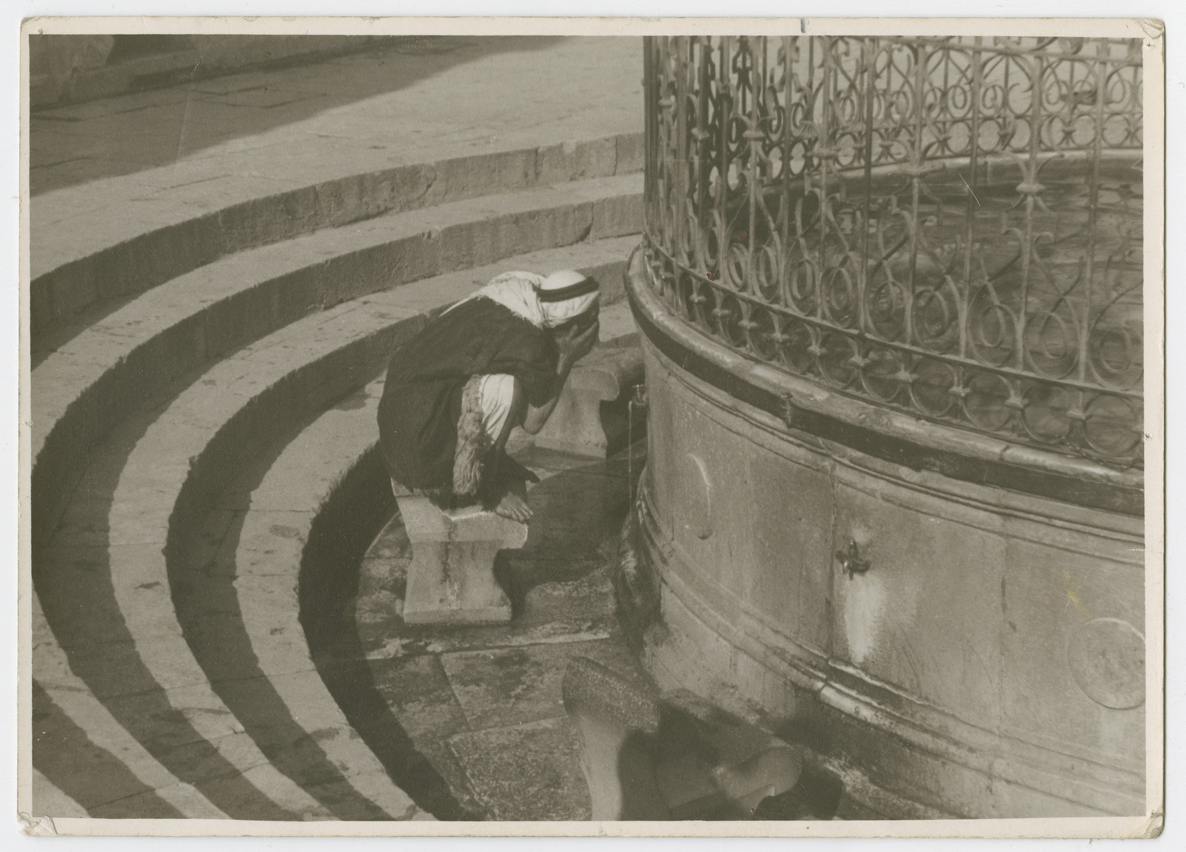 "An Arab man washes at a fountain [possibly outside the Dome of the Rock].  Photograph is used on page 278 of Robert Gessner's ""Some of My Best Friends are Jews."" The pencil inscription on the back of the photograph reads, ""Ar Temple.""e"