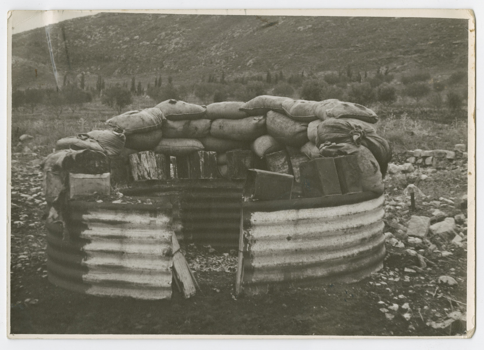 "View of a crude fort made of metal sheet and sandbags protecting a settlement in the Valley of Jezreal.   Photograph is used on page 195 of Robert Gessner's ""Some of My Best Friends are Jews.""  The typed caption attached to the photograph reads, ""Crude fortress protecting Zionist collective farm in the Valley of Esrraelon [sic]."""