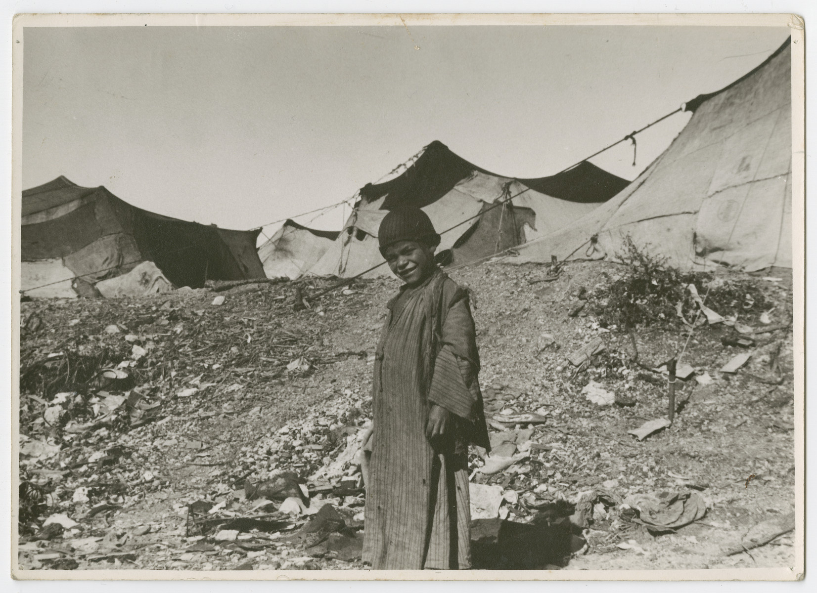"A child, (probably from a Sephardic home), stands outside a tent colony.  Photograph is used on page 197 of Robert Gessner's ""Some of My Best Friends are Jews."""
