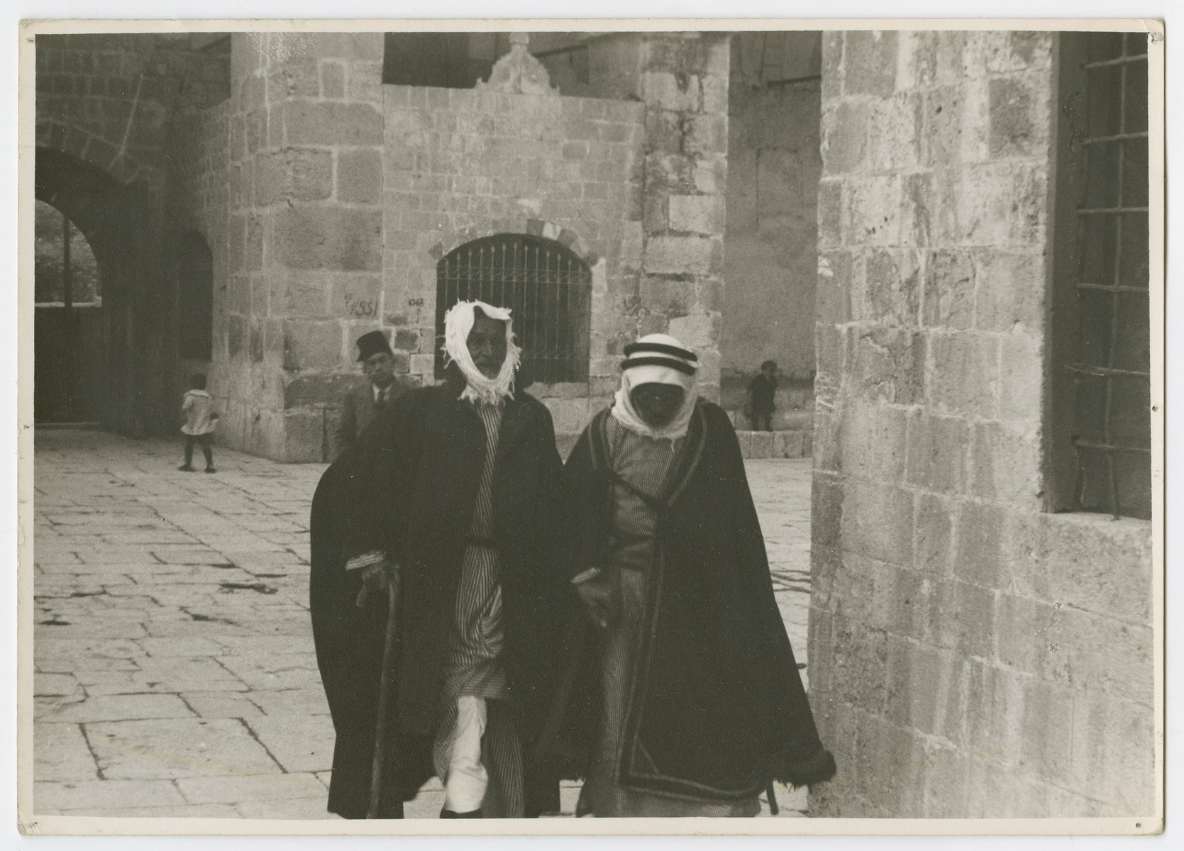"Two Arab men walk through a courtyard, probably in Jerusalem.  Photograph is used on page 242 of Robert Gessner's ""Some of My Best Friends are Jews."""
