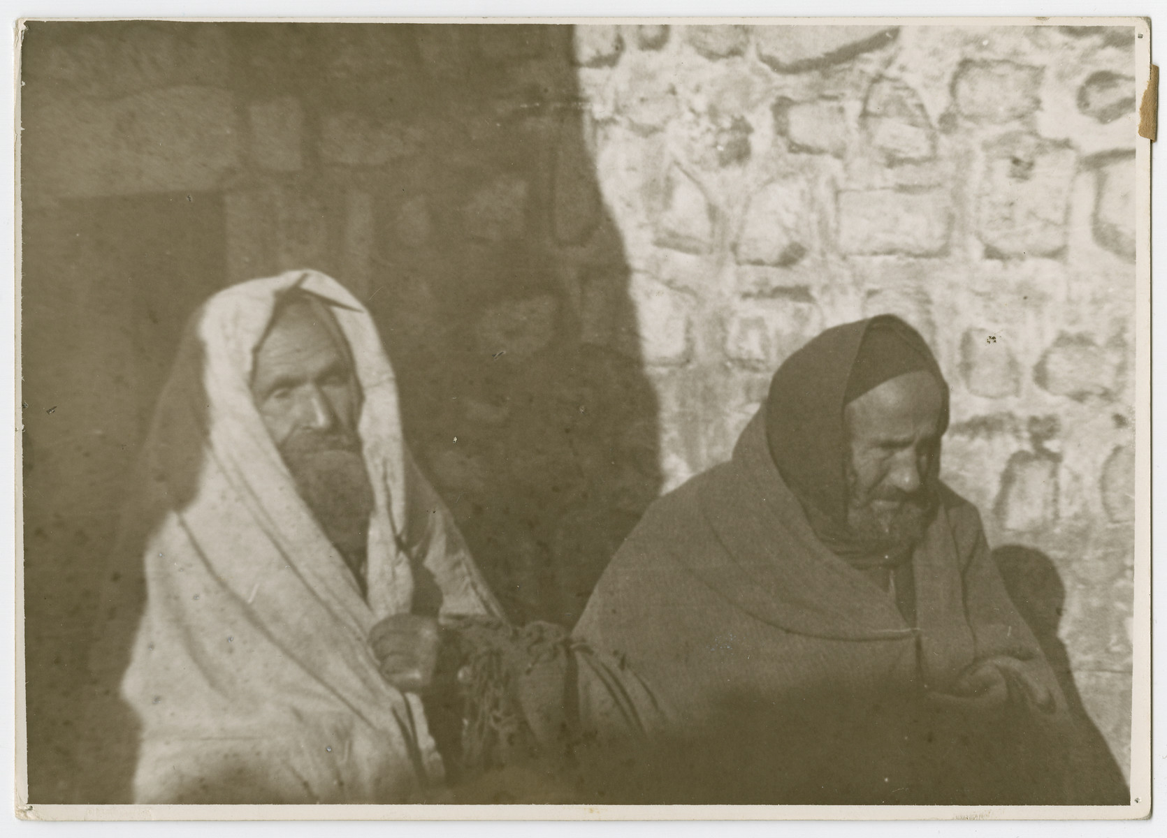 "Close-up portrait of two impoverished Jewish men.   Photograph is used on page 242 of Robert Gessner's ""Some of My Best Friends are Jews."" The pencil inscription on the back of the photograph reads, ""Jewish Beggar."""