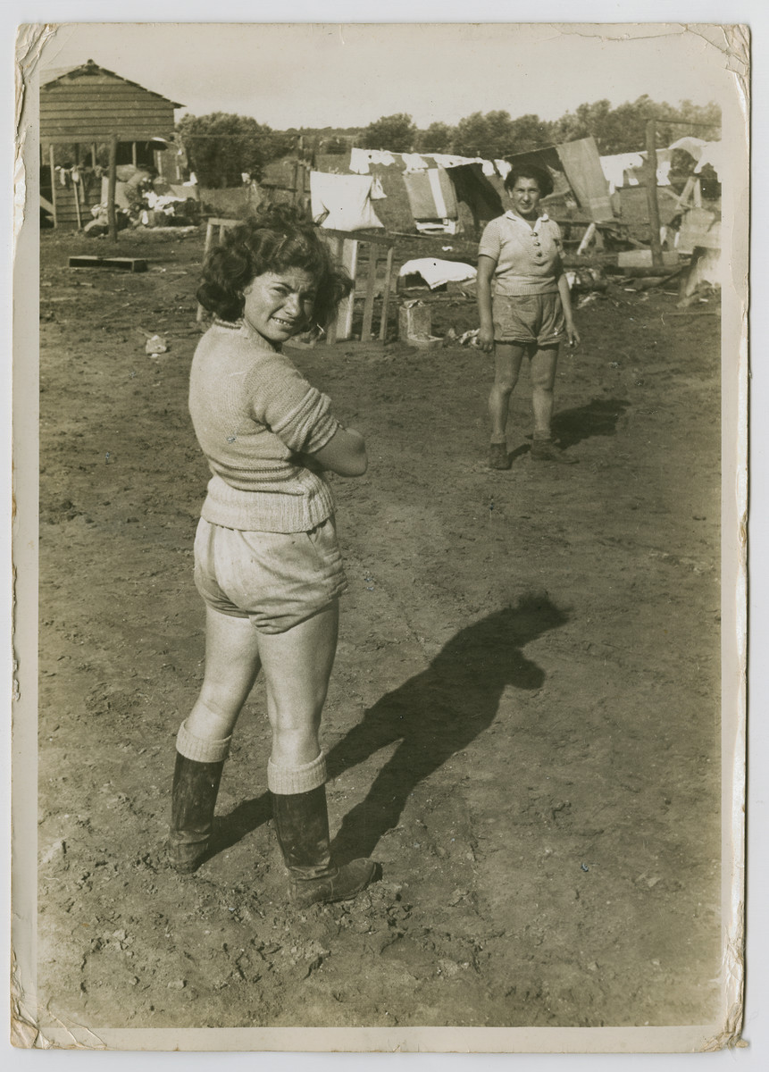 "Two woman stand in a muddy field in front of a laundry line in a new settlement, possible Hadera.  Photograph is used on page 197 of Robert Gessner's ""Some of My Best Friends are Jews."" The pencil inscription on the back of the photograph reads, 'Farm Palestine."""