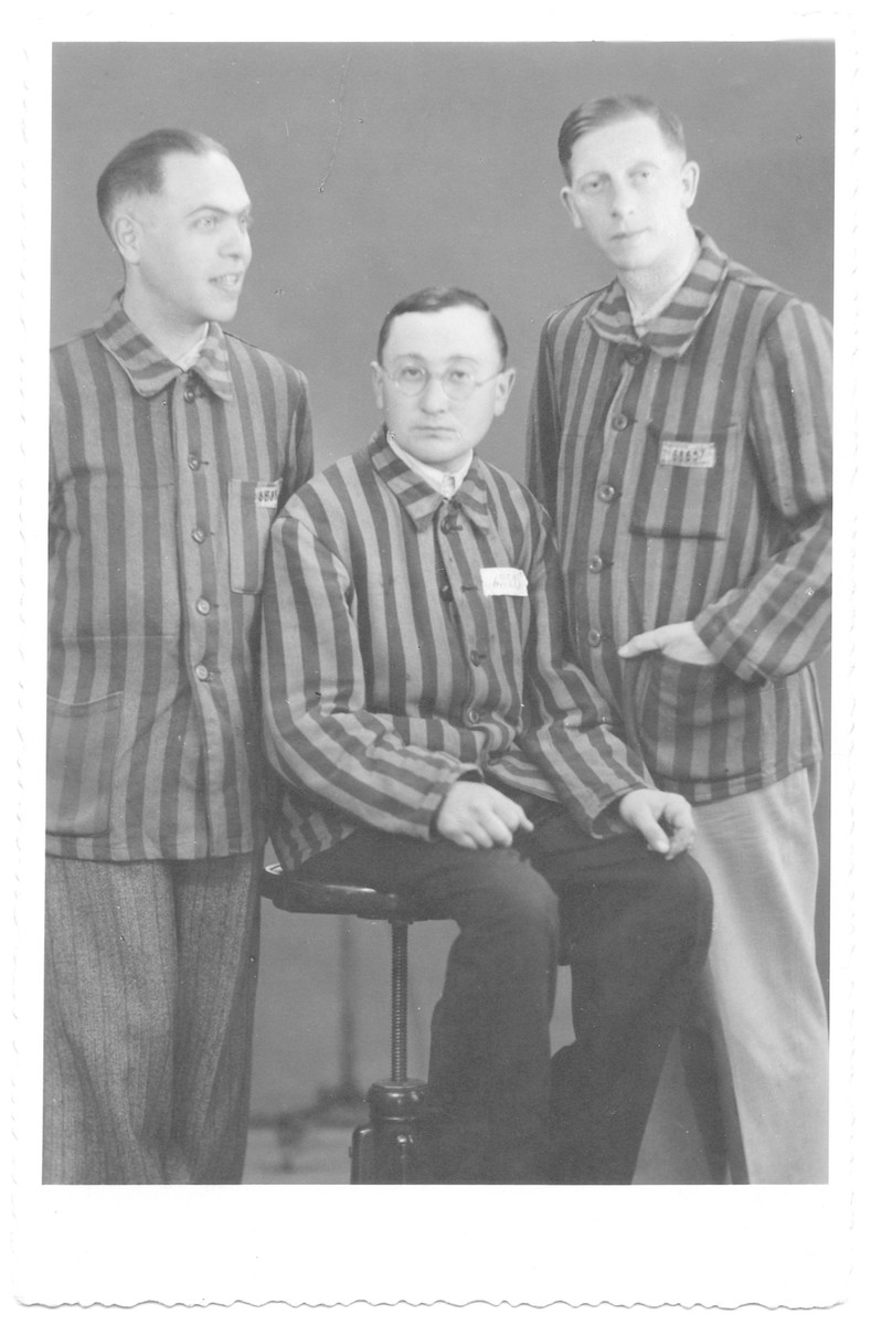 Three survivors pose for a studio portrait in their camp uniforms after liberation.  From left to right are Josef Sperling, Moniek Gelb amd Alfred Ungar.