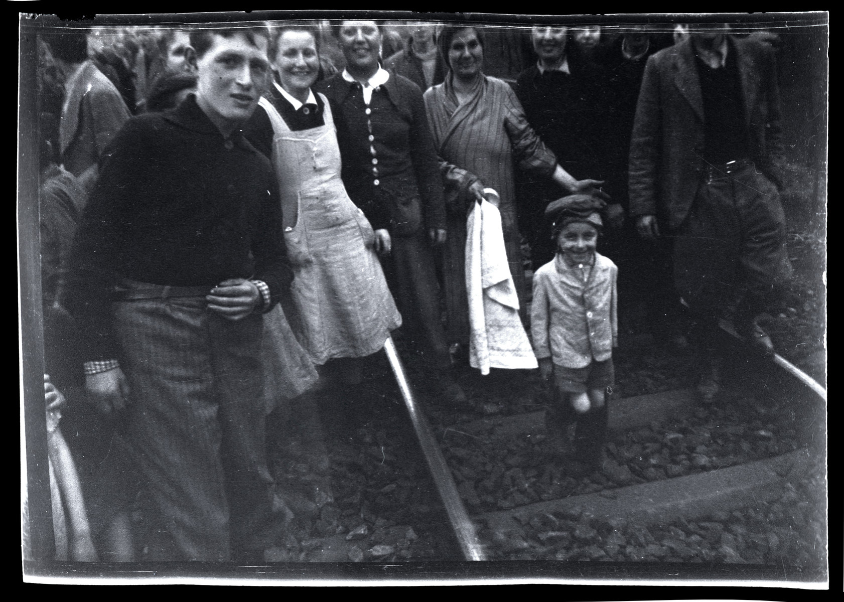Survivors from Bergen-Belsen pose by the train tracks shortly after their liberation.