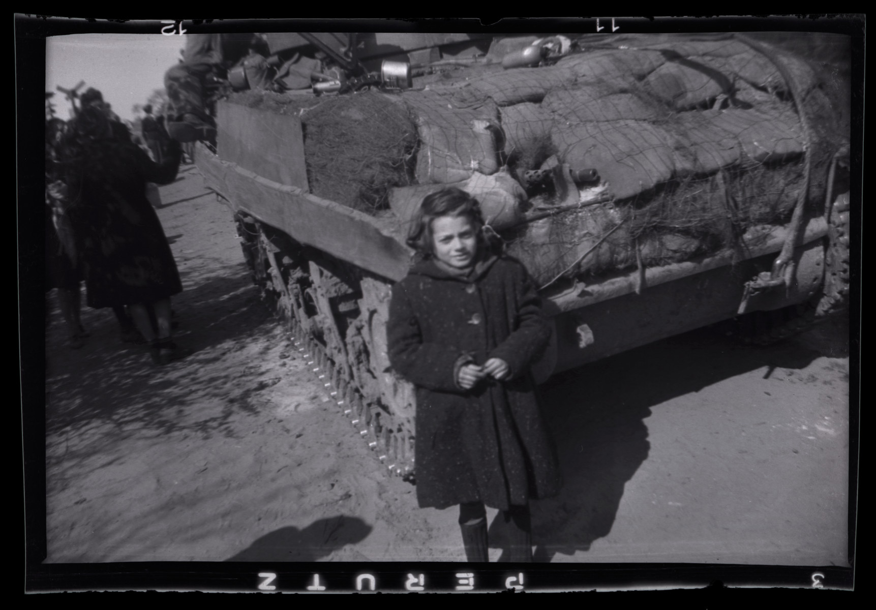A young girl stands next to an American tank shortly after her liberation.