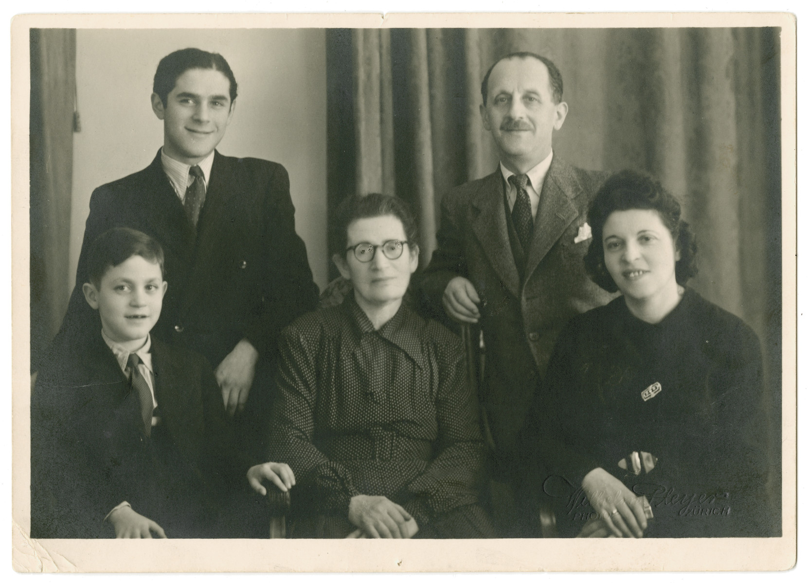 Studio portrait of an extended family of Jewish refugees in Switzerland.    Seated left to to right are Fred Gross, Rachel Reichert Kempinski, and her daughter Nacha Gross.  Standing are Leo and Max Gross.