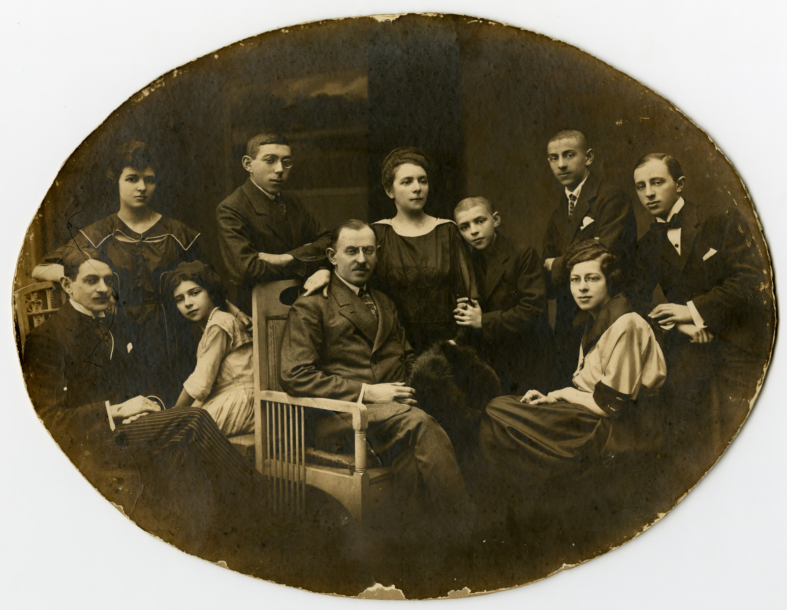 Studio portrait of the family of Wolf Percik.   Pictured from left to right are (standing) Rosalie Percik Lubawski, Zygmunt Percik, Dora Percik, Ludwik Lew Percik, Maximilian Percik, and Henry Percik;  (seated) Stanislaw Lubawski, Irena Percik Rosenkrantz, Wolf Percik, and Felicia Percik.   Of the people pictured, only Irena Percik Rosenkrantz and Stanislaw Lubawski survived the Holocaust.