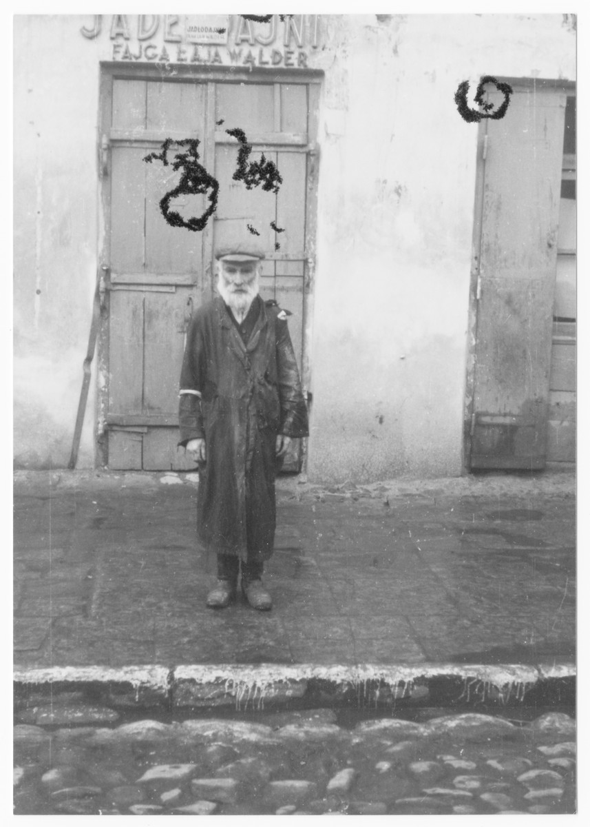 An elderly Jewish man stands in front of the entrance to a building in the Lublin ghetto.