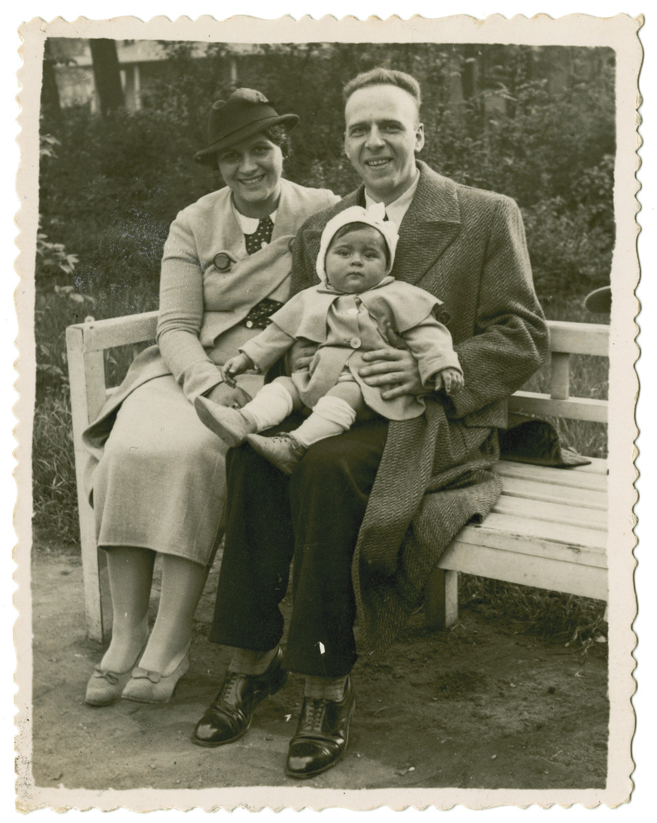 Tola and Maurice Reinberg sit on a park bench with their baby daughter Halina.