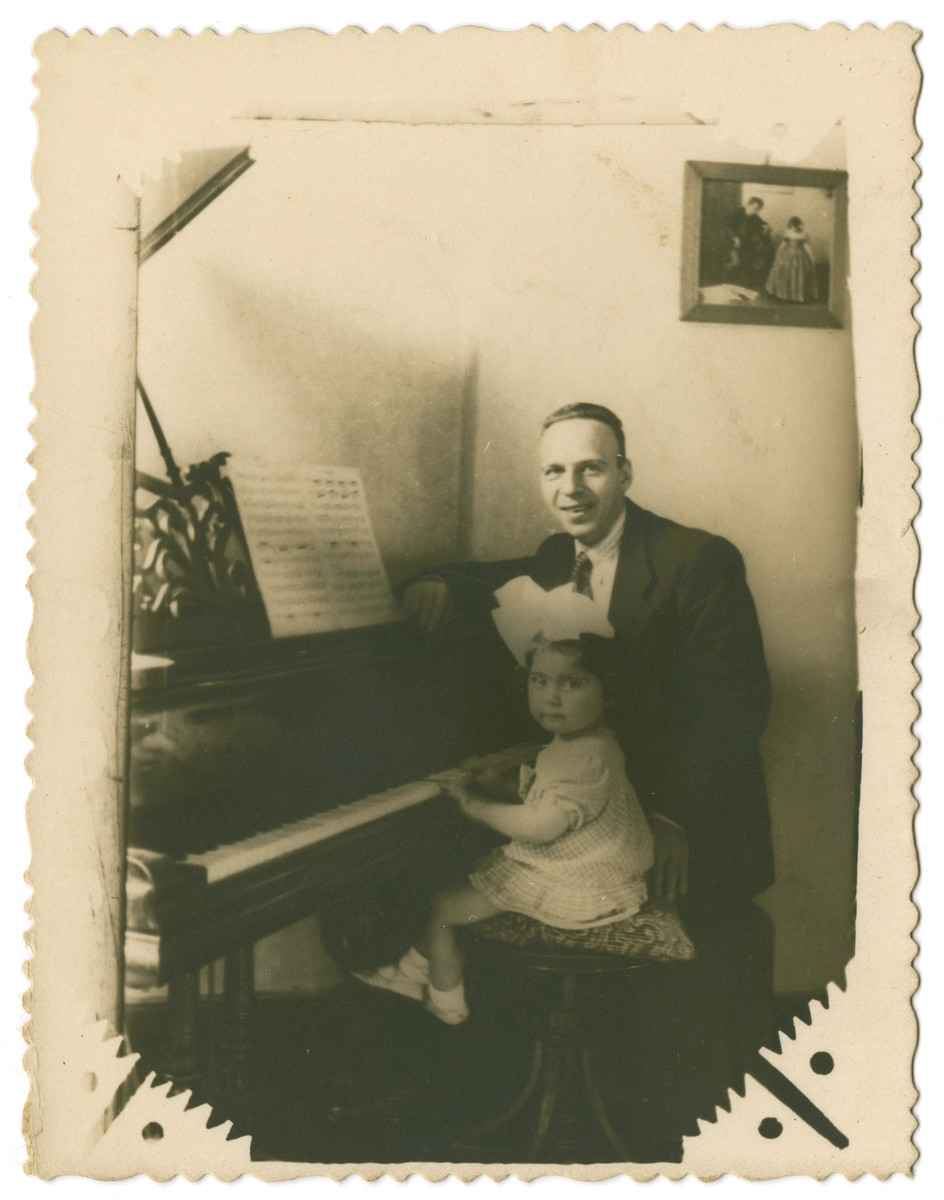 Maurice Reinberg sits by the piano with his small daughter Halina.