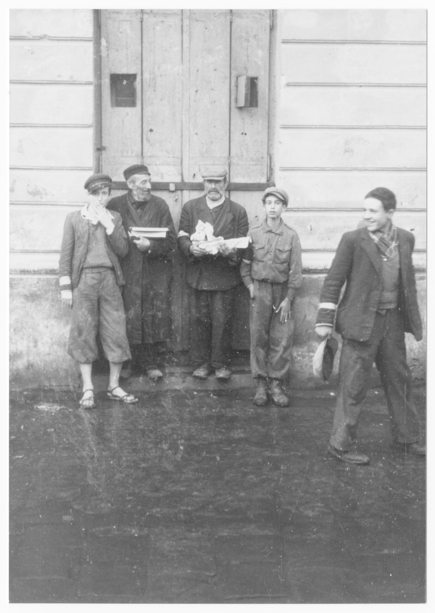 A group of Jewish men stand outside a building in the Lublin ghetto.