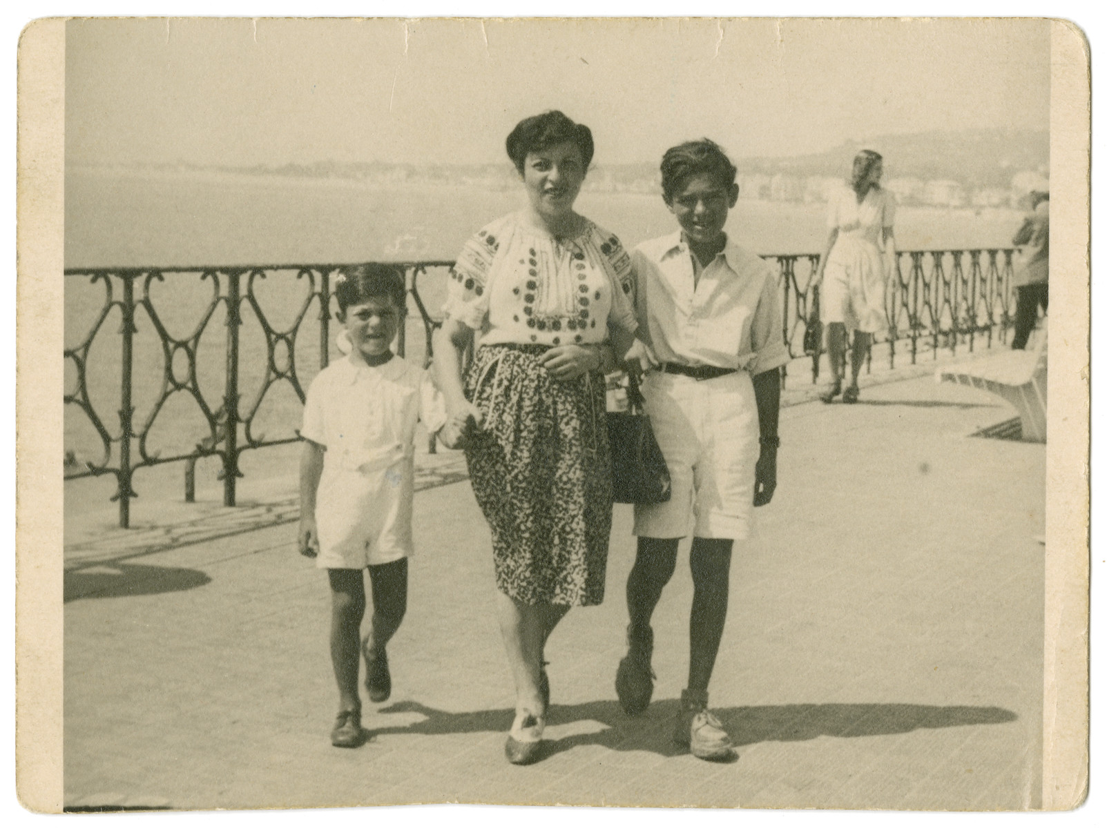 Nacha Gross walks along the sea shore in Nice acompanied by two of her sons, Fred and Leo.