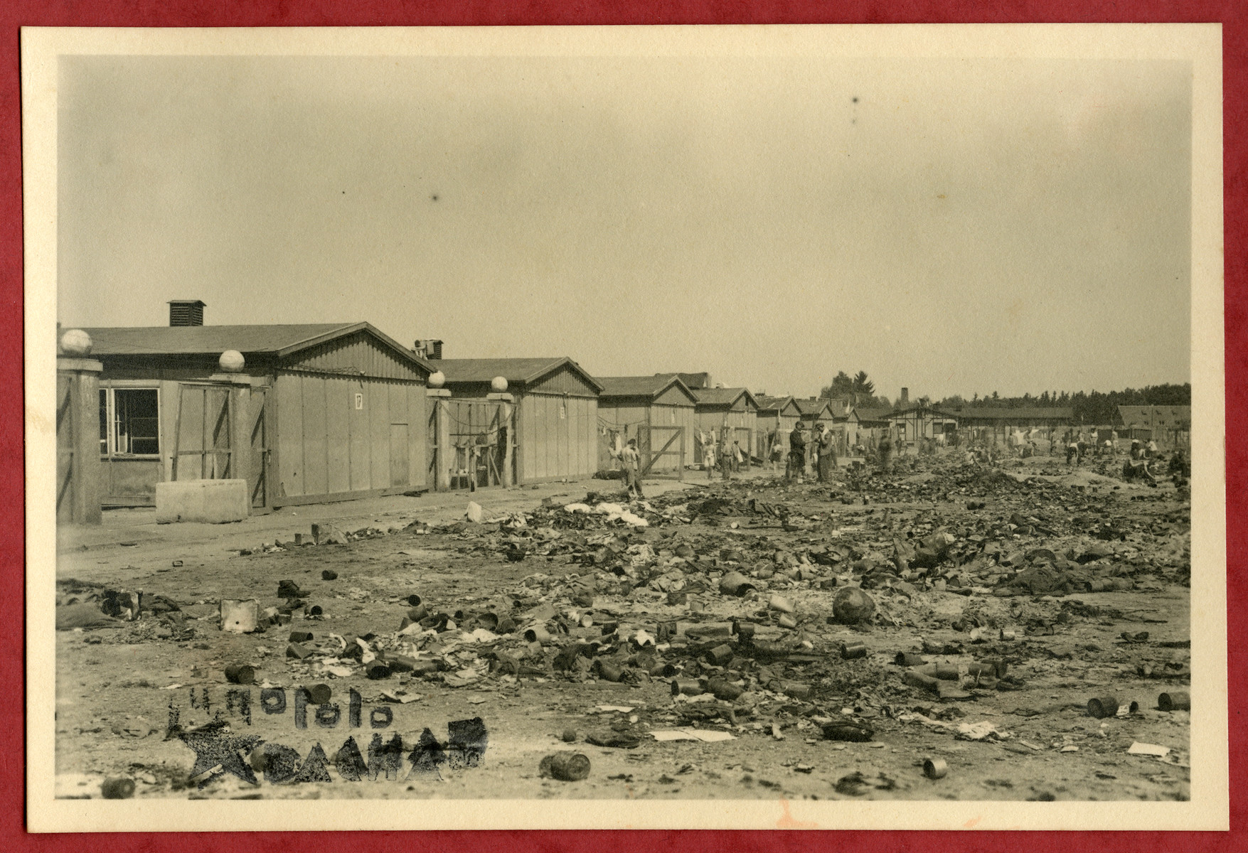 Photograph showing debris outside a row of barracks in the Dachau concentraton camp pasted into an album presented to Lt. Col. Martin Joyce by the Yugoslav prisoner committee.