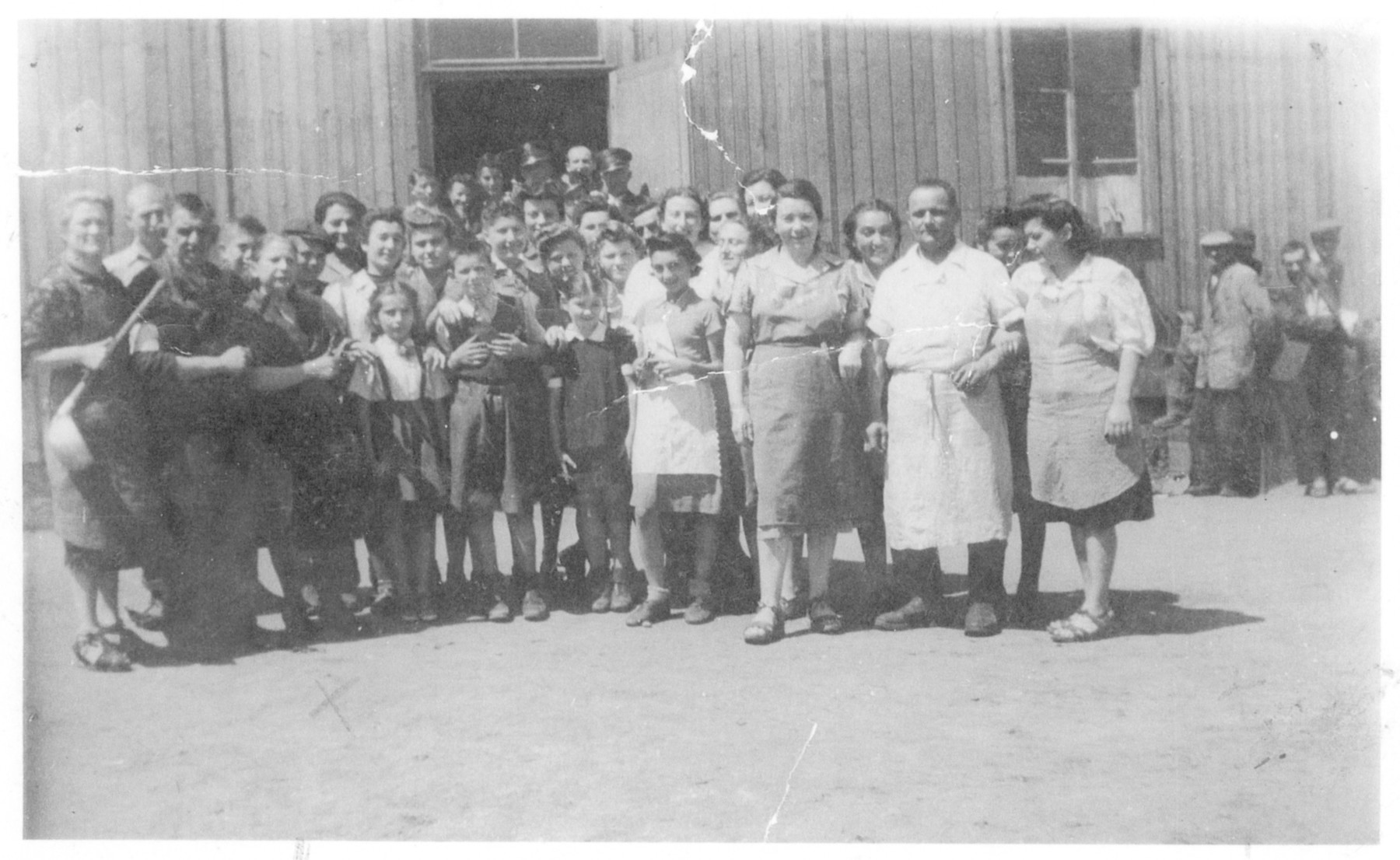Group portrait of men, women and children of the Prokocim labor camp in Krakow.  Helen Ungar is standing in the fron row.  Her brother Adam is next to her.  The camp cook is standing second from the right.  To his left is Stefania's sister Lucia and to his right are Stefania and her sister Jula.