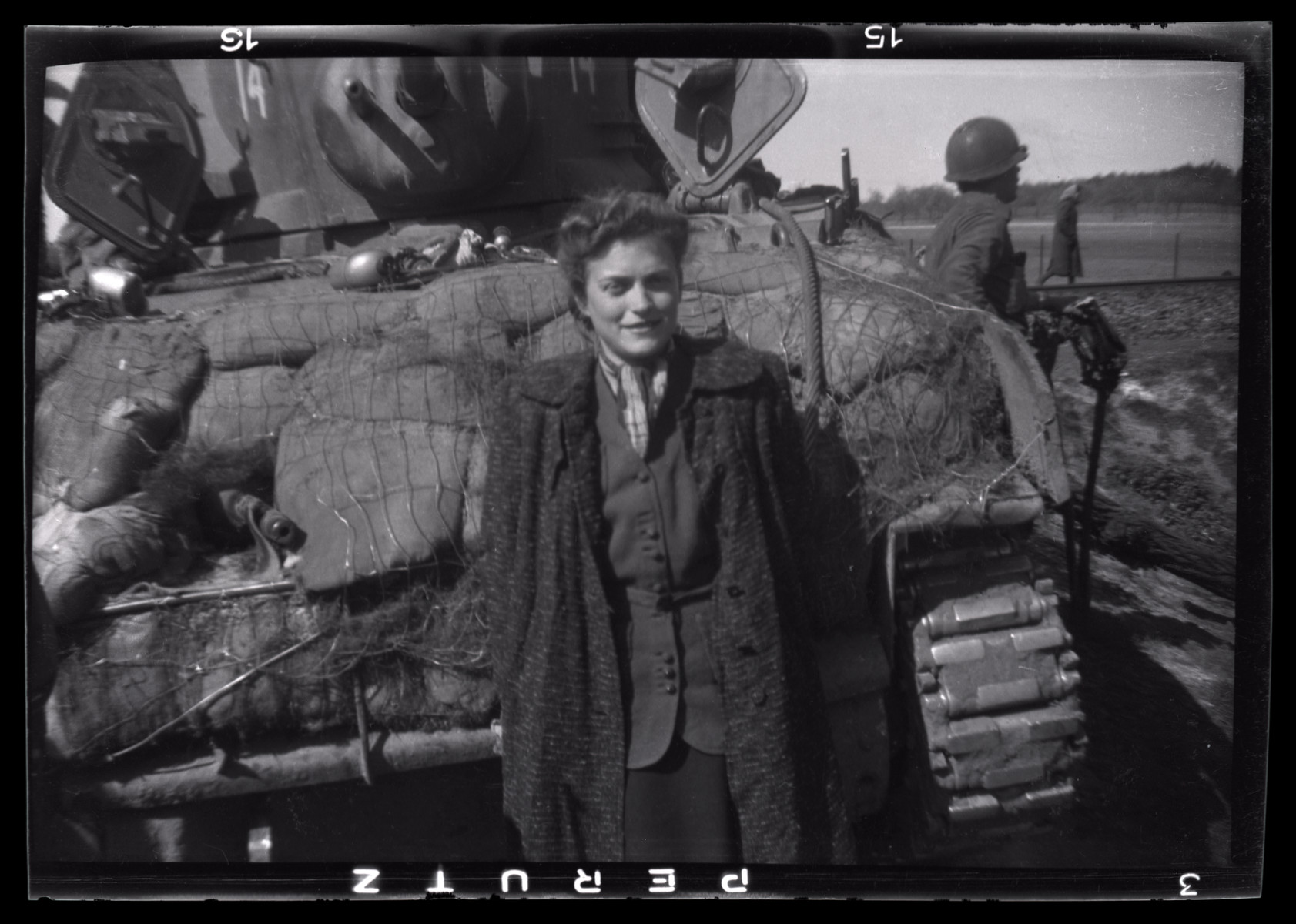 Gina Rappaport (later Leitersdorf) stands next to an American tank shortly after her liberation.  She had survived the Warsaw ghetto prior to her incarceration in Bergen-Belsen.  Fluent in several languages, she translated for the Americans and other survivors of the train.