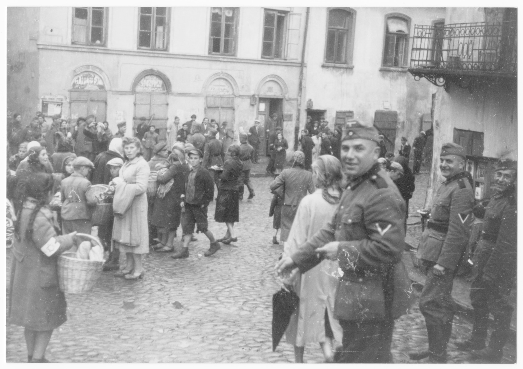 German soldiers watch Jewish women shop at the outdoor market of the Lublin ghetto.
