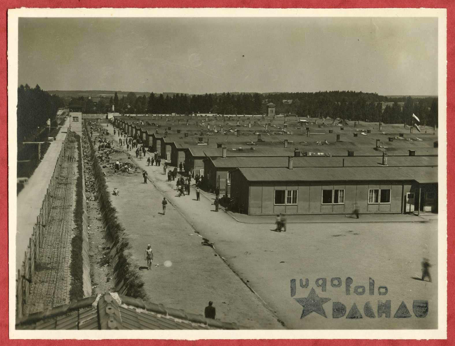 Photograph showing a view of the Dachau concentration camp pasted into an album presented to Lt. Col. Martin Joyce by the Yugoslav prisoner committee.
