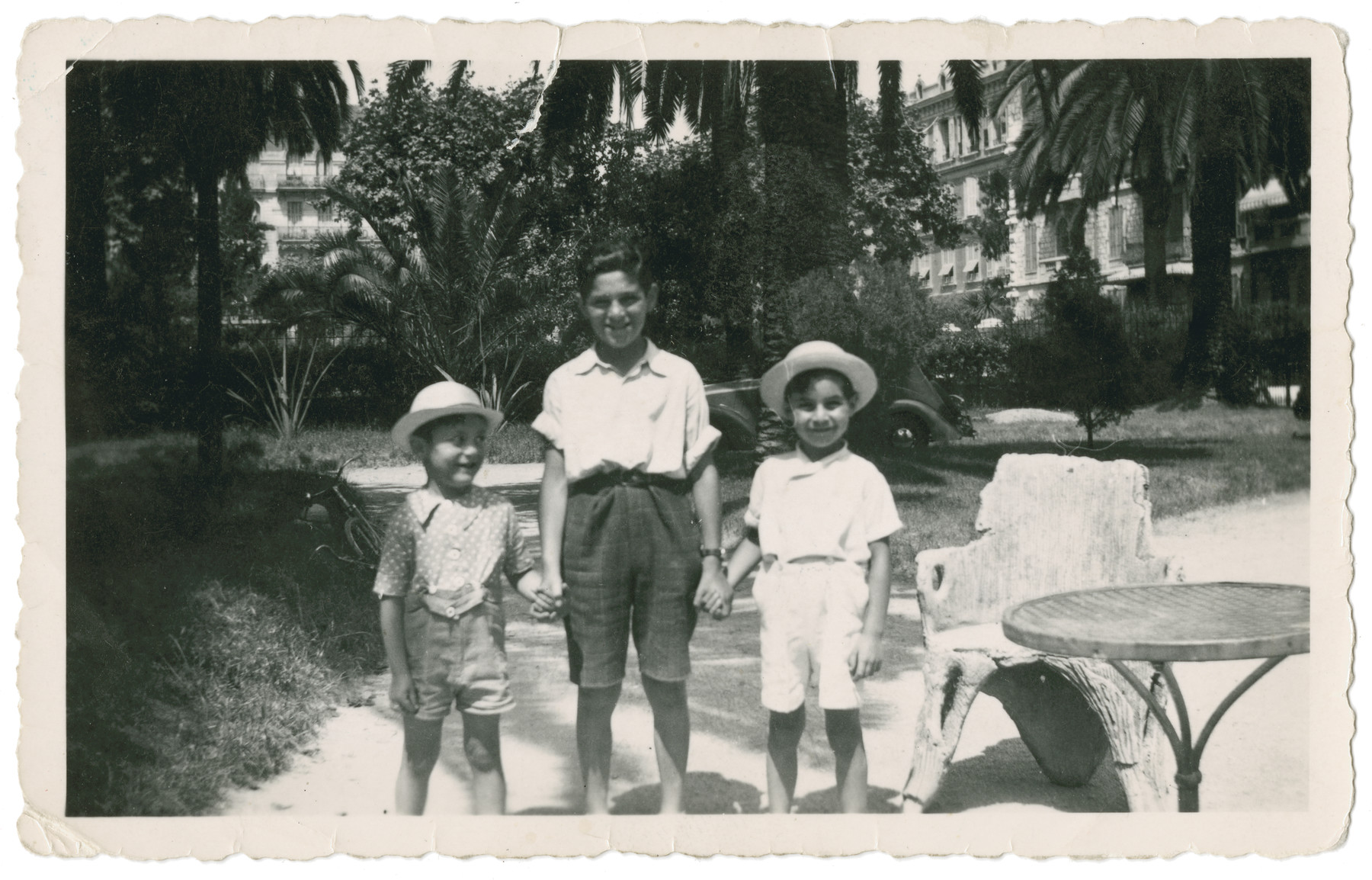 Three boys pose underneath the palm trees of the Hotel Continental in Nice.  From left to right are Fred and Leo Gross and their friend Mikey Abet.