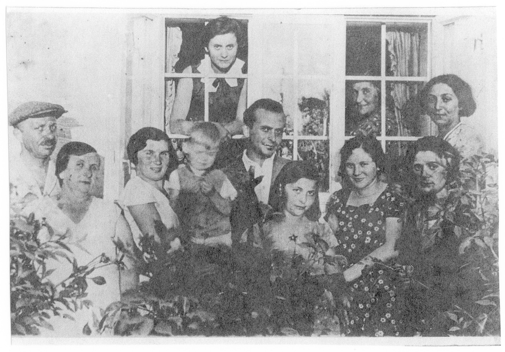 Group portrait of relatives of Stefania Ungar in her parents' home in Bolchowka.  Her sister Irka is third from the left.  Nex to her is Adam.  Her sister Jula is looking through the window.  Stefania is in the front, right.  Her sister Lucia is behind her and her mother Zosia is looking out the window on the right.