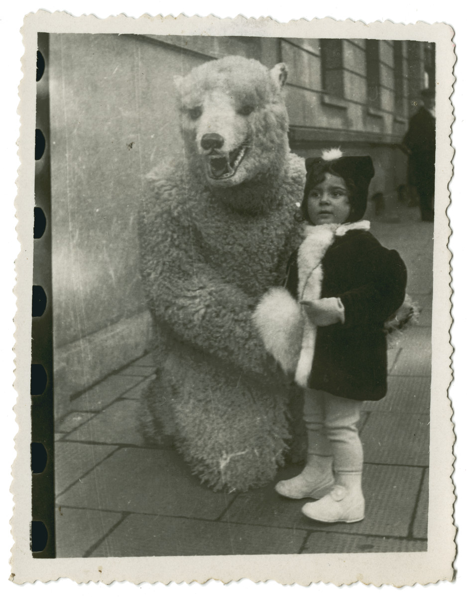 Halina Reinberg poses with someone dressed in a bear costume shortly before leaving Poland with her parents.