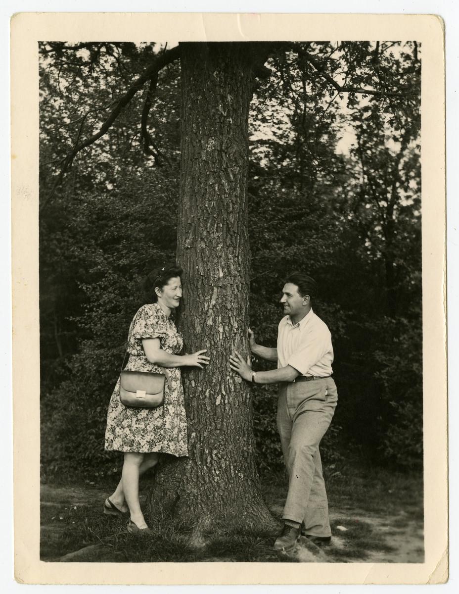 Nachman and Miriam Sadik pose on opposite sides of a tree.