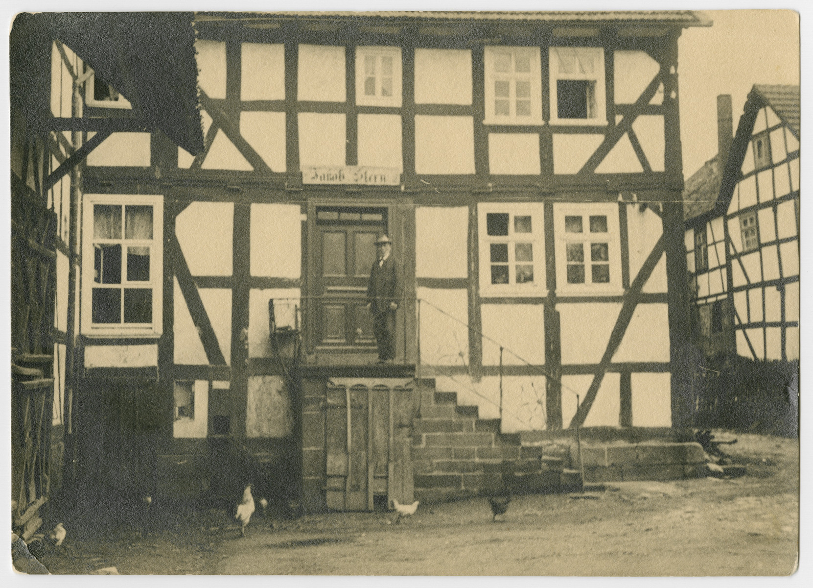Jakob Stern stands before the entry to his home in Gilserberg, Germany.