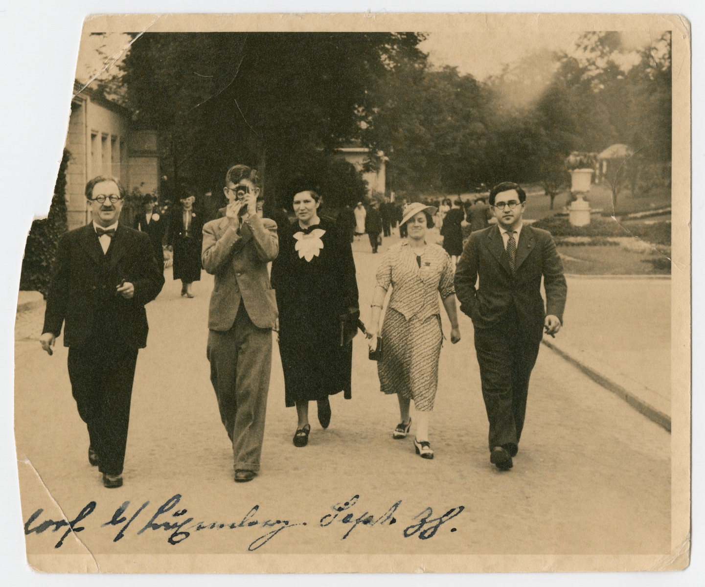 A German-Jewish family walks down a street in Luxembourg.  Norbert Isenberg (with camera) walks between his parents Sally and Erna. His brother Artur and an unidentifed woman, likely Hildegard Suesskind, are pictured at right.