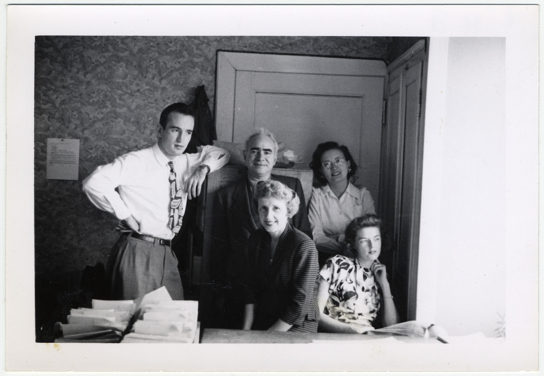 Maurice Levitt, a member of the Frankfurt Jewish GI Council, and four members of his staff work in their office in Bad Nauheim.  Maurice Levitt is standing in the center.  Else Jordan is in front of him.