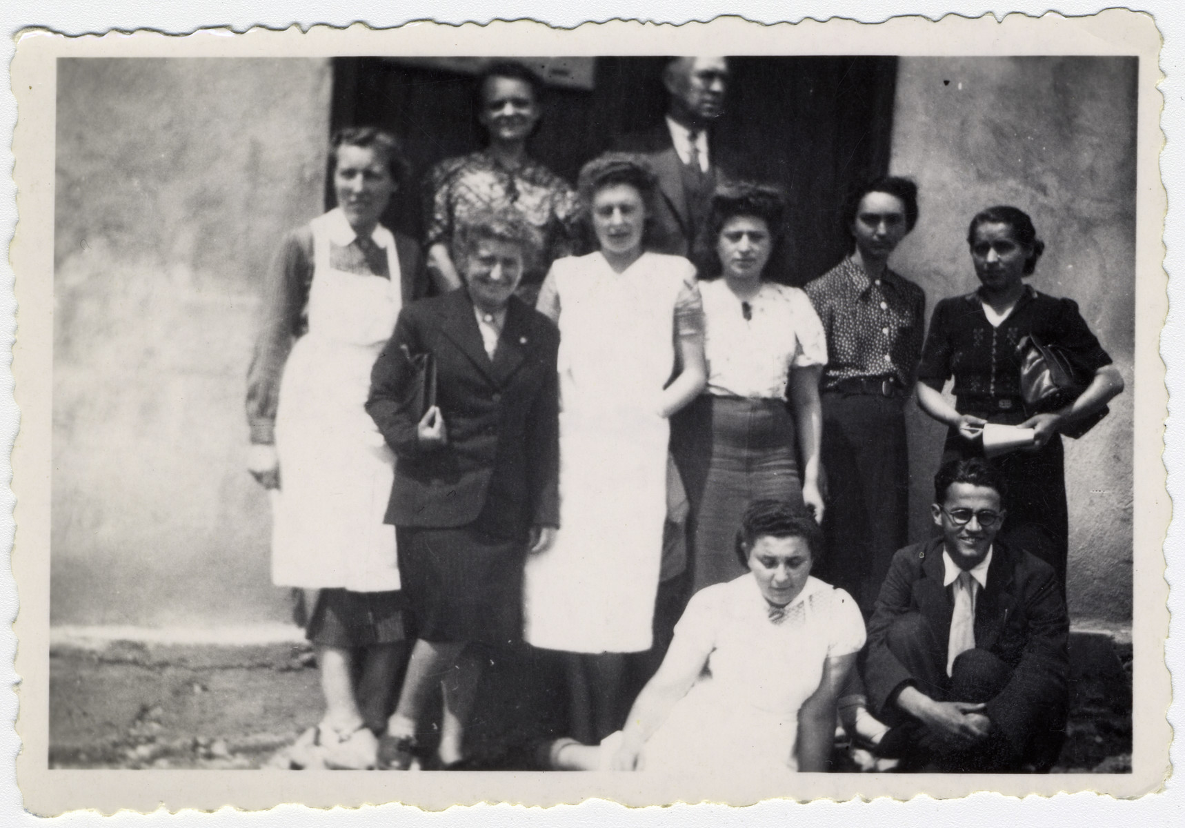 """Volunteer resident social workers and OSE staff pose for a group portrait  in the Rivesaltes internment camp.   Original caption reads: """"The workers."""""""