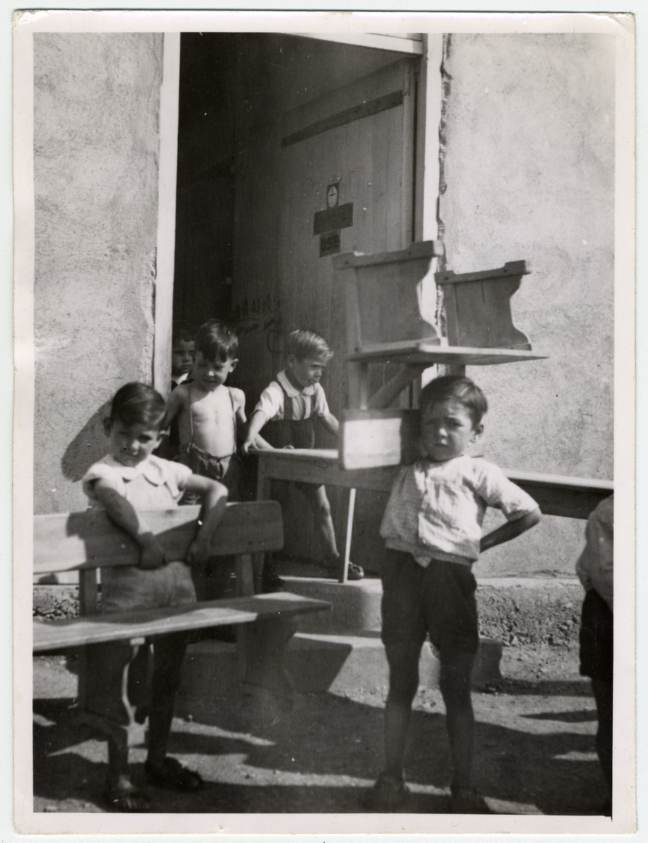 "Several young boys help move classroom furniture--a table, a bench, and a chair--outside, at the Rivesaltes internment camp.   Original caption reads: ""Nursery School."""