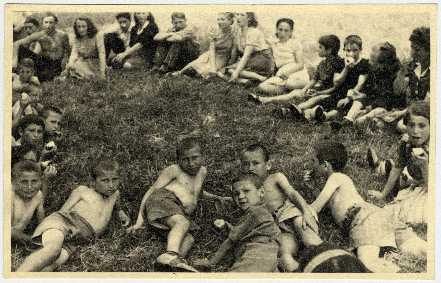"Children [probably from the Lindenfels camp] rest on the lawn during an excursion to Koenigstein Castle.  Original caption: ""Rest period during a picnic at Koenigstein Castle."""