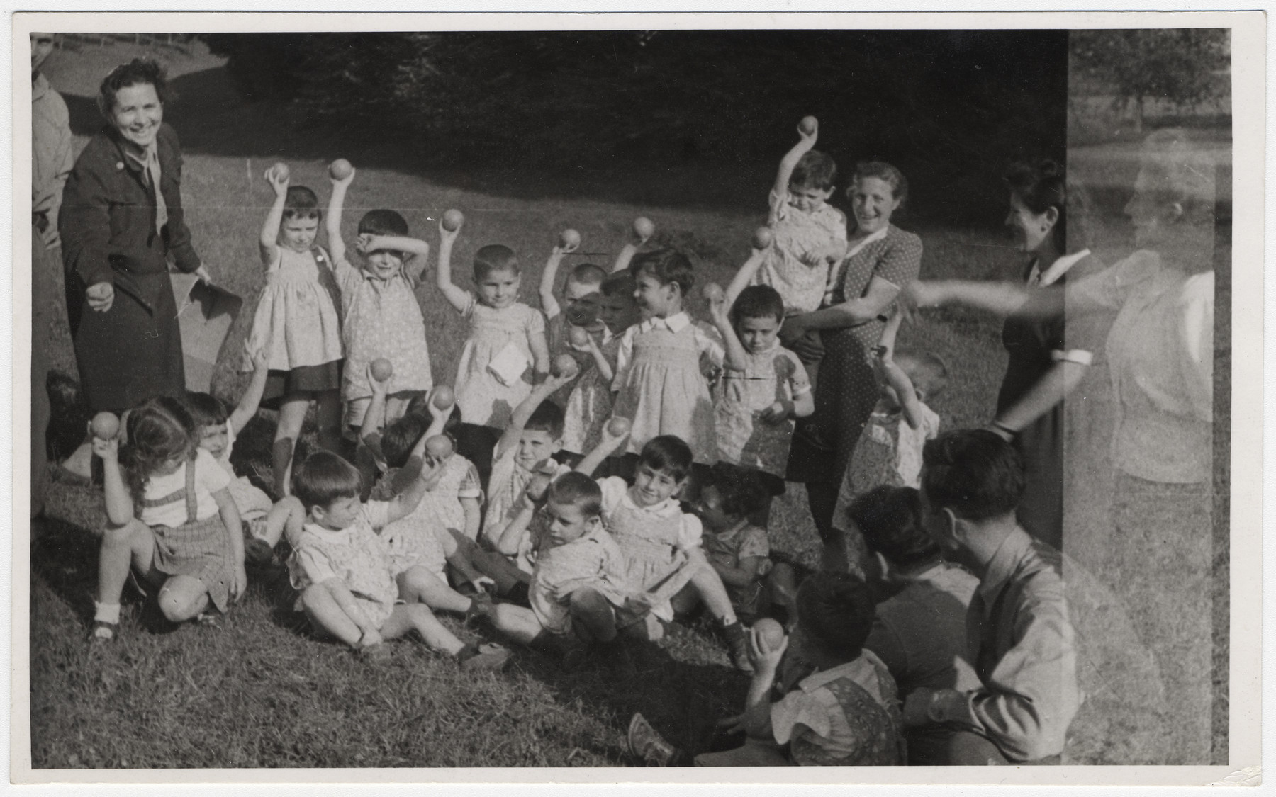 Young children [probably from Lindenfels] hold up pieces of fruit they received during an outdoor excursion.