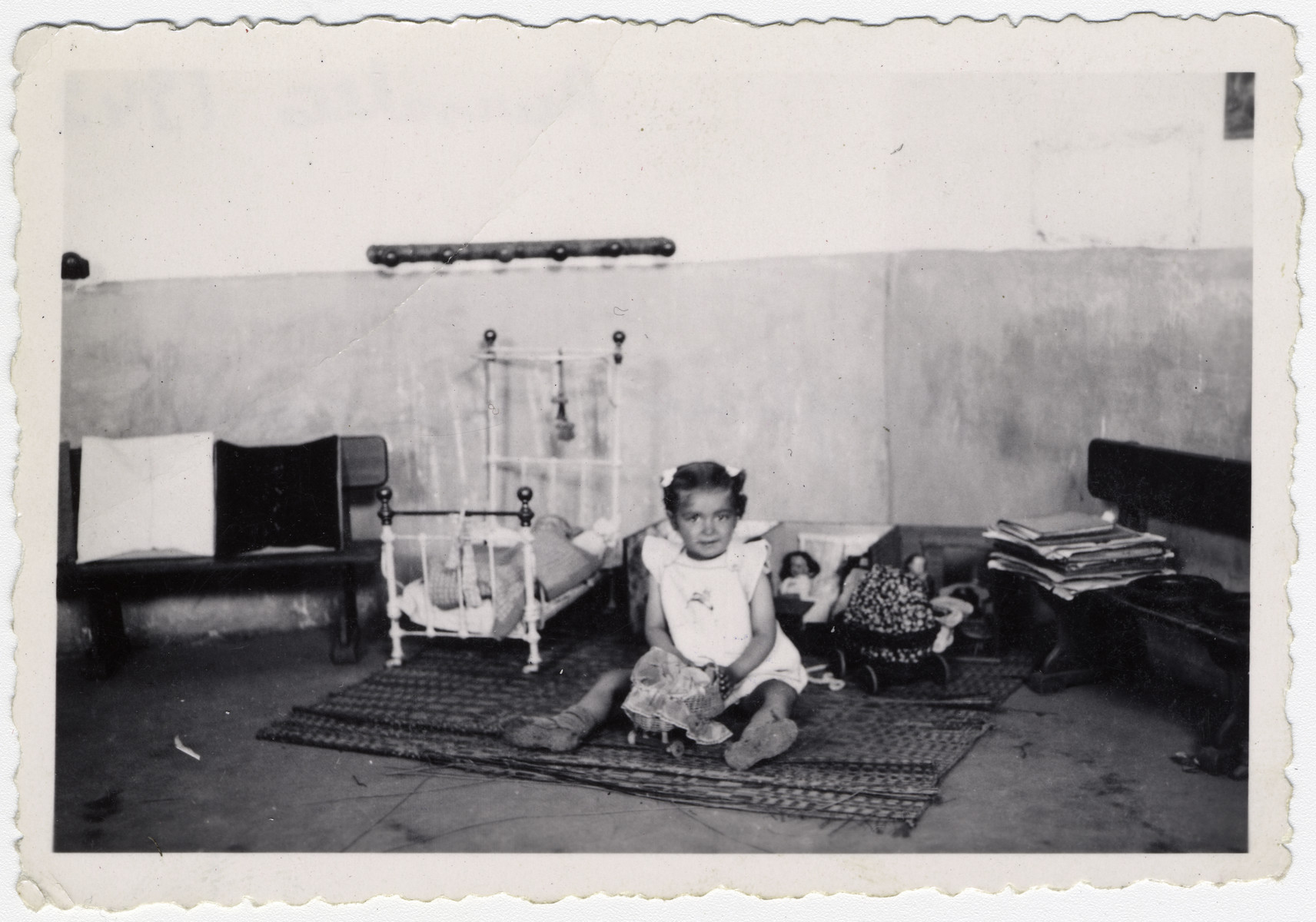 "A young girl interned at Rivesaltes sits on the floor of a play room,  fiddling with her dolls. Original caption reads: ""Josephine playing with her toys."""