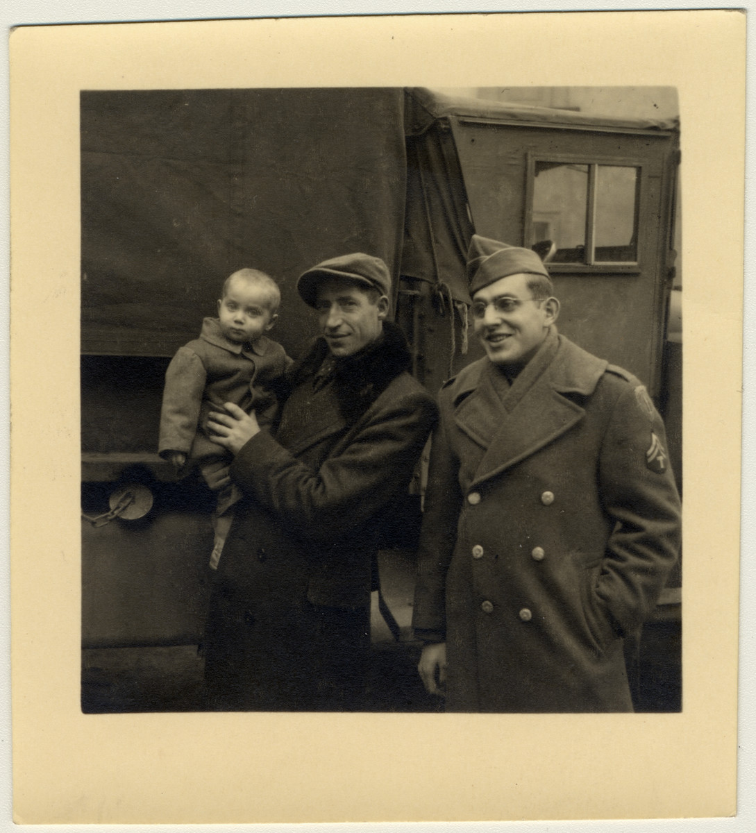 A member of the Frankfurt Jewish GI Council poses with a Jewish displaced person holding his young child.