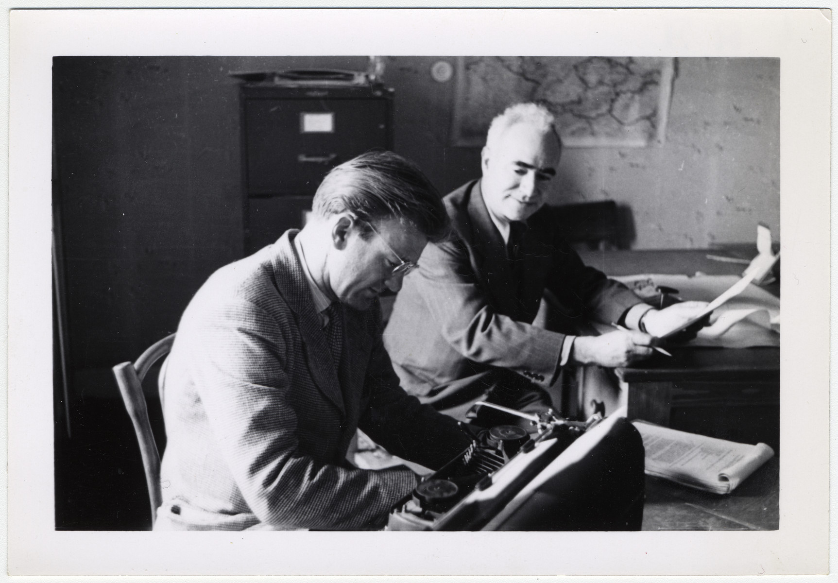 Maurice Levitt (right), a member of the Frankfurt Jewish GI Council, and his secretary work in their office in Bad Nauheim.