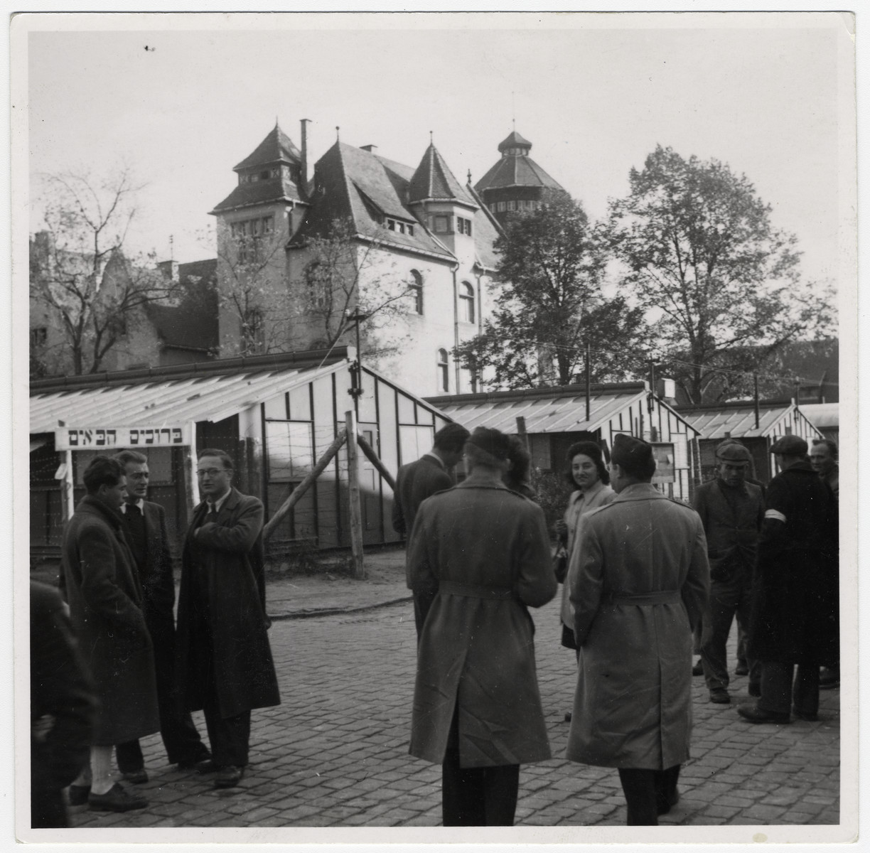 People gather in a public square in front of a castle.  A welcome sign in Hebrew is on the left.