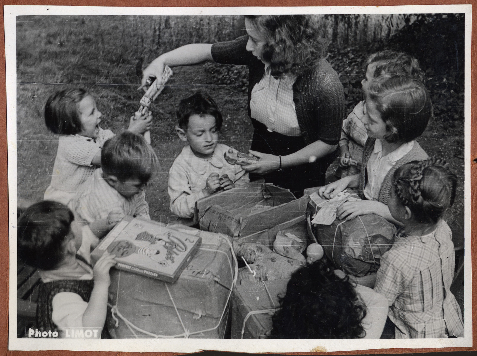 A group of children gather around their caretaker as they open packages filled with toys.