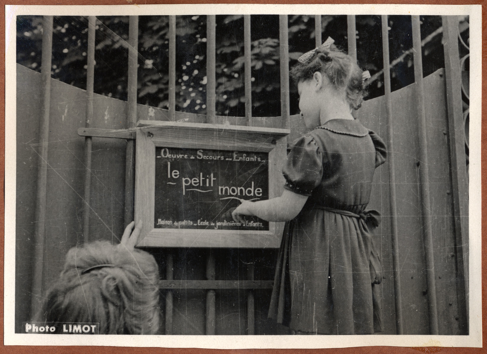 A young girl reads a sign outside the OSE children's home, Le Petit Monde.