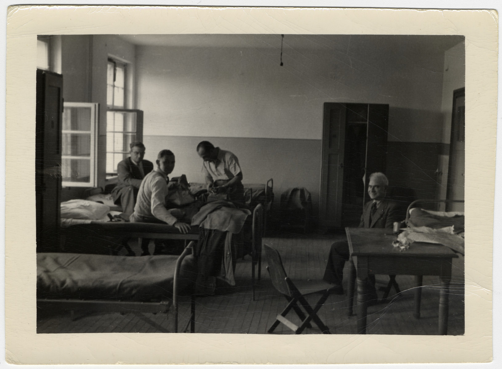 Maurice Levitt sits by a table while others gather on cots in the dormitory in Bremerhaven.