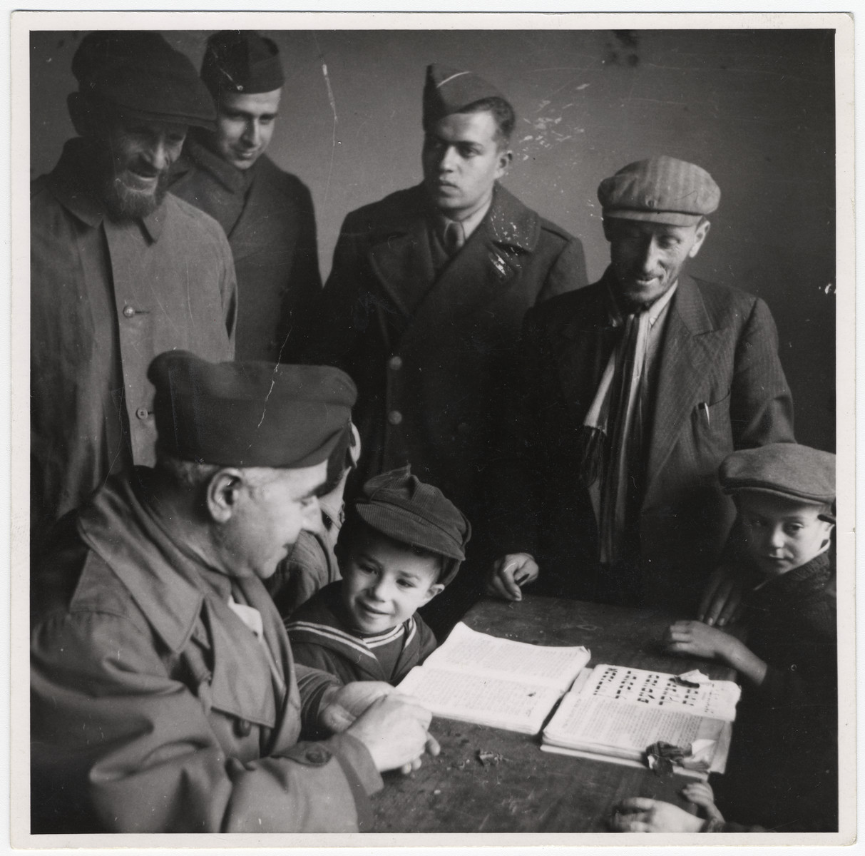 "Maurice Levitt and other members of the Frankfurt Jewish GI Council meet with young religious boys learning Hebrew in Dieburg.  David Marcus' original caption reads: ""A young student tells a Council member what he has learned during the day."""