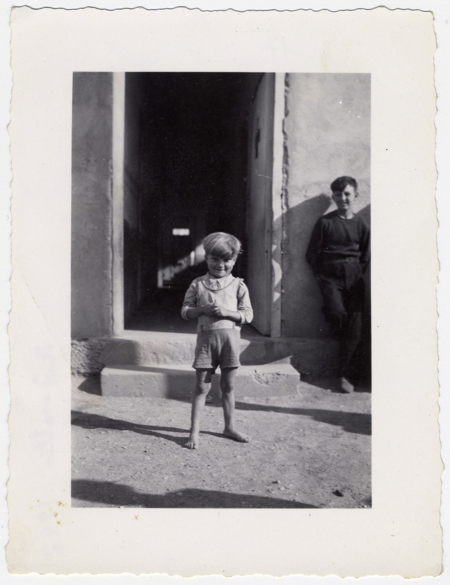 A small boy smiles as he stands outside a building at the Rivesaltes internment camp.