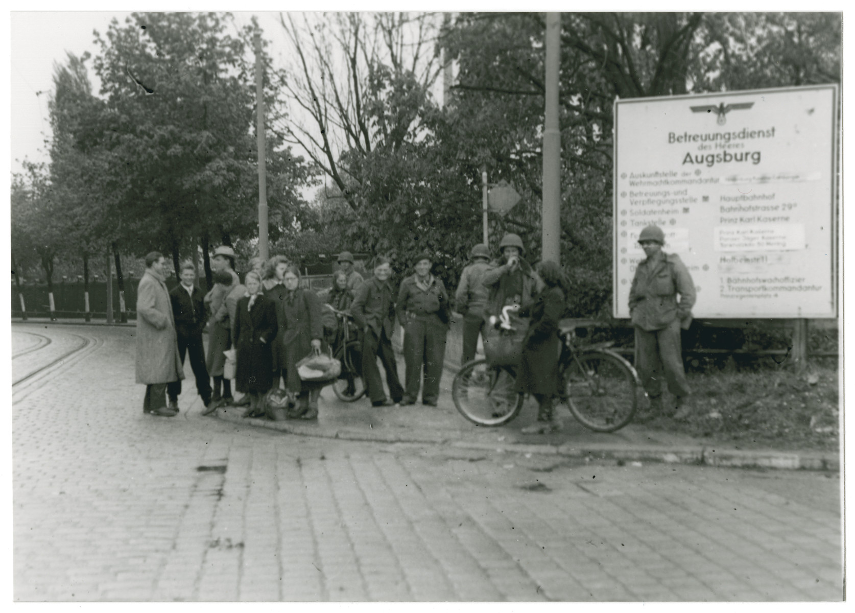 Civilians and American soldiers gather on a street corner of Augsburg in front of a sign with a Nazi eagle to watch American tanks removing obstacles.