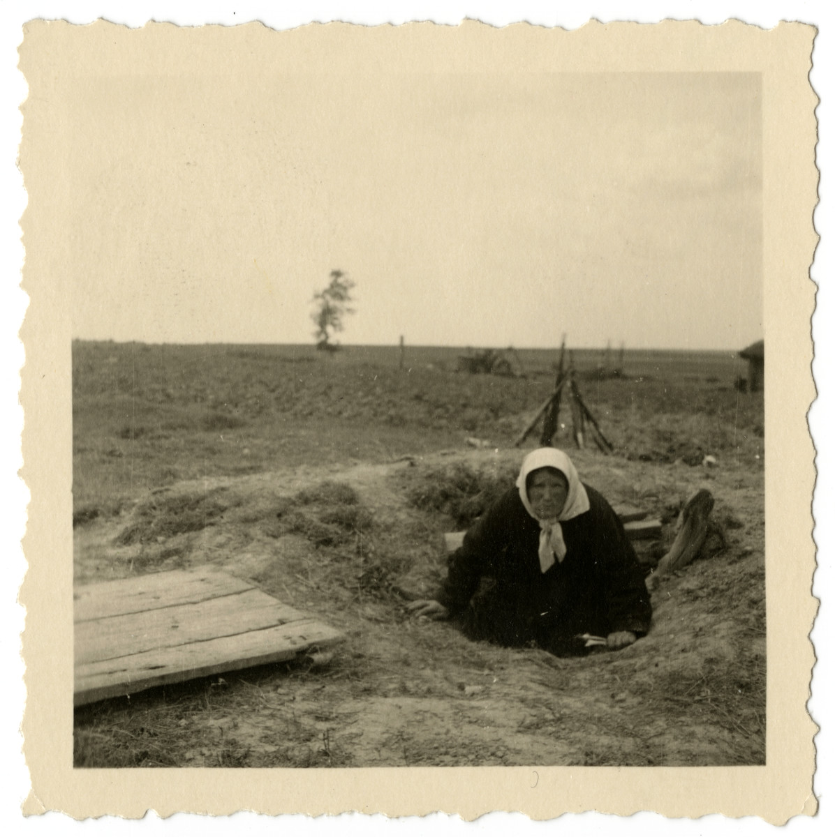 A woman emerges from an underground bunker in a field in an unidentified location.