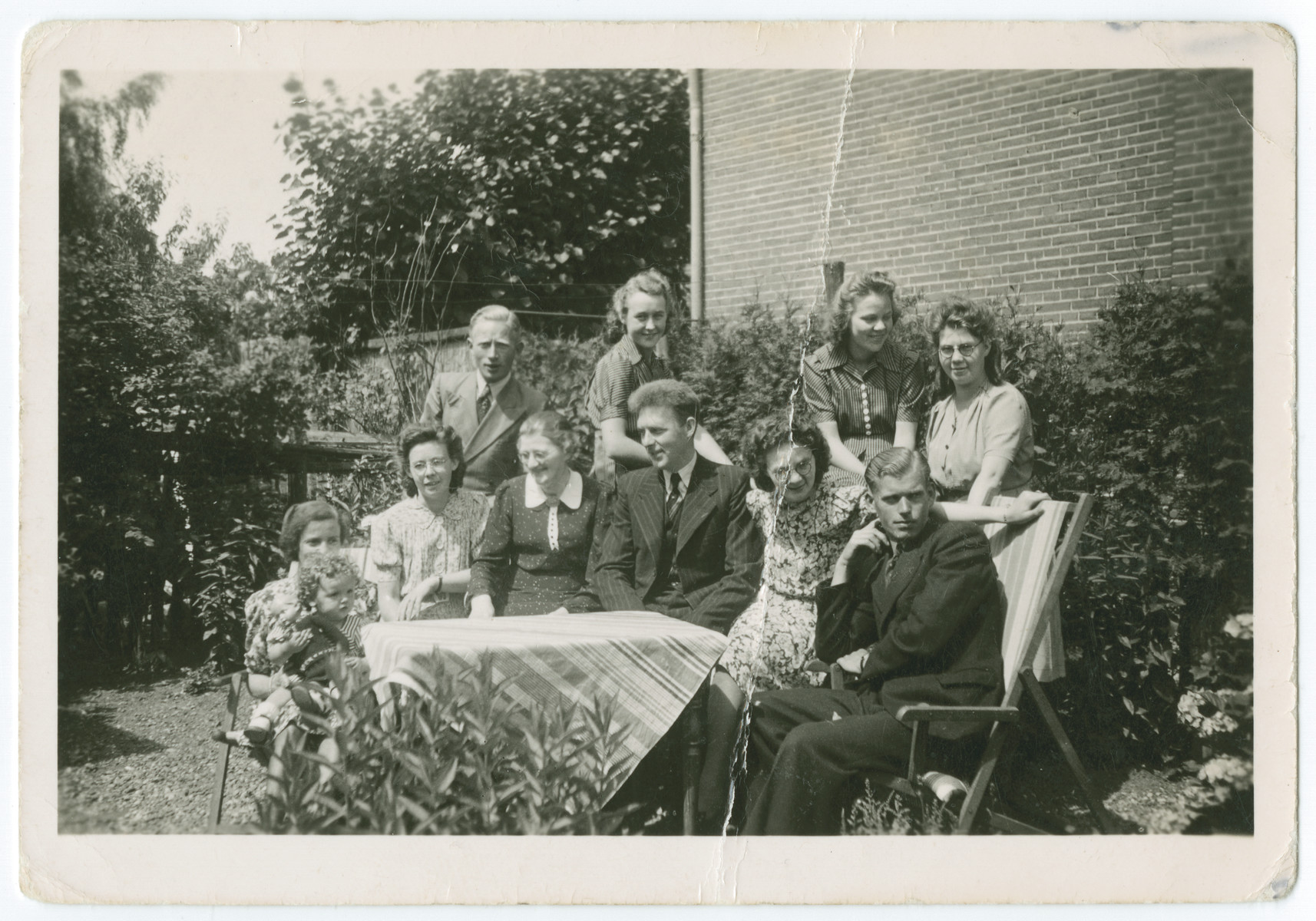 Young people gather outside on the property of the Beuving family, the rescuers of the donor and her sister.  Tiema and Alie Beuving are on the left.  The building in the background was a butcher shop frequented by the Nazis.