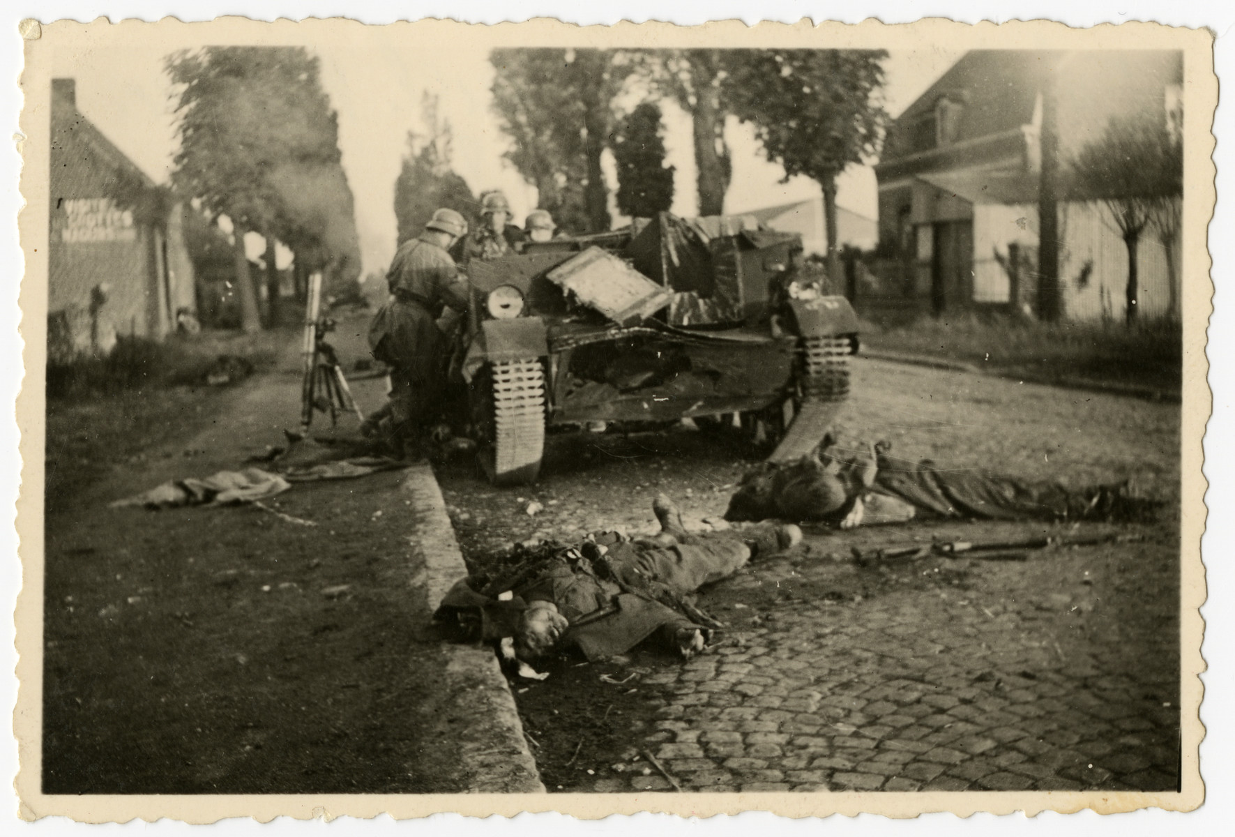 "German soldiers look at a damaged and disabled British tank in front of the corpses of two soldiers.  The original caption reads ""Erledigter eng Panzer"""