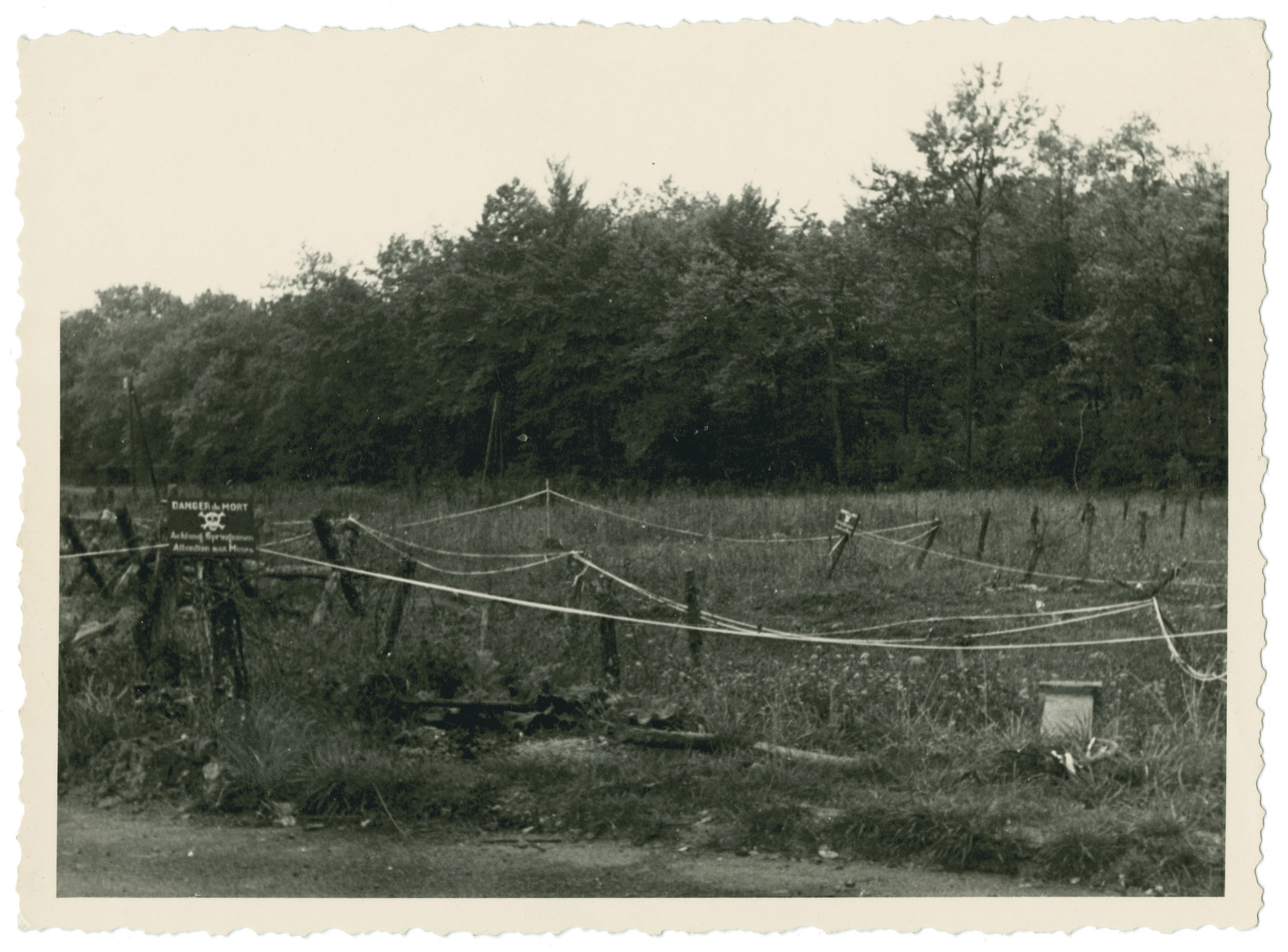 View of a field [perhaps a mine field] surrounded by wire fence and a sign in French warning of danger of death.