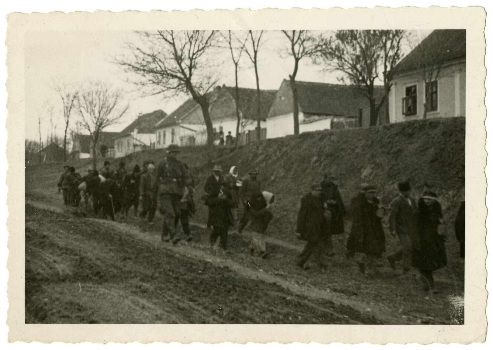 A German soldiers escorts a column of people in an unidentified locale.